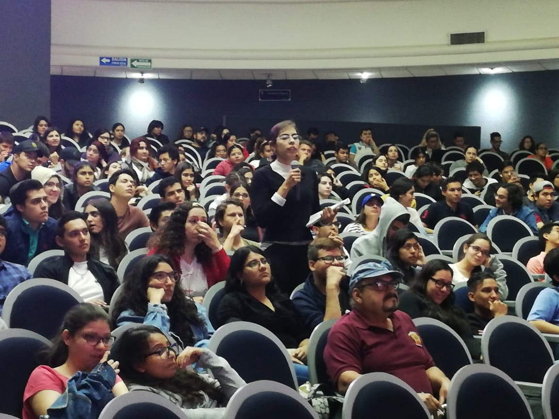Vista general de los asistentes a la conferencia. Una alumna de pie tomando la palabra