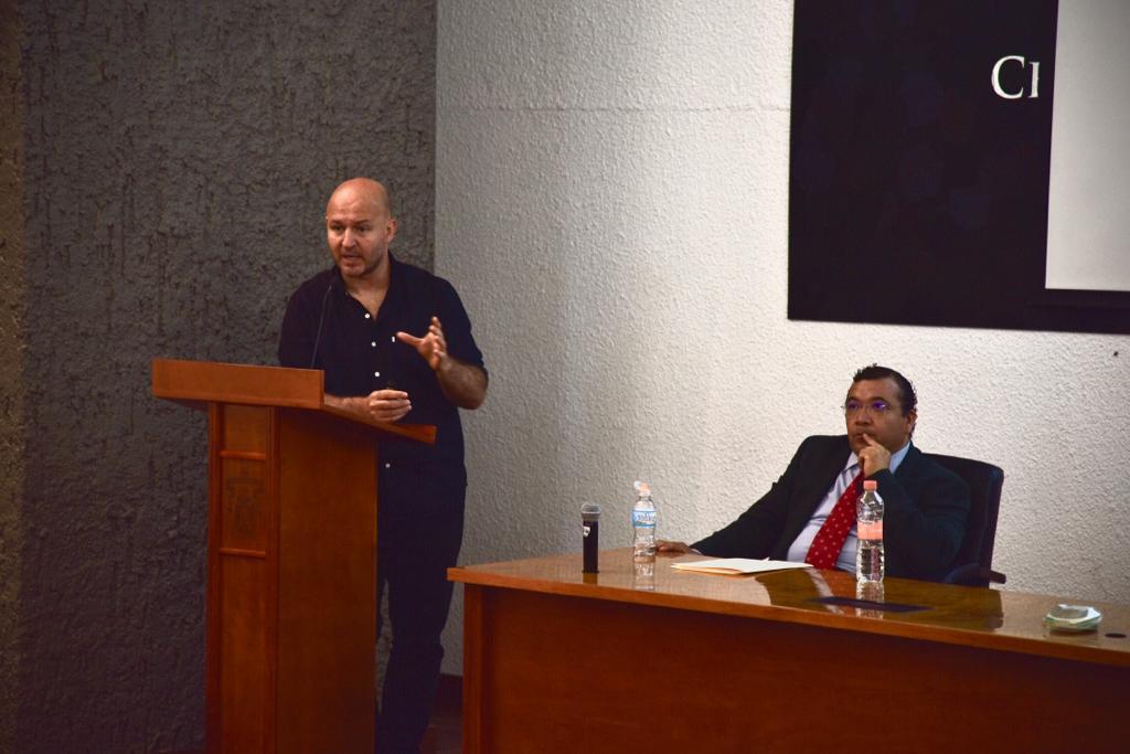 Ponente impartiendo conferencia, una diapositiva se ve en la pantalla