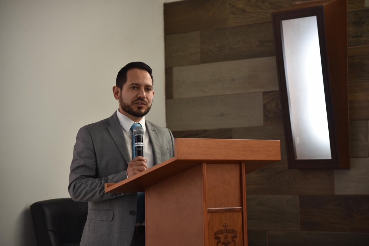 Coordinador de la Licenciatura en Medicina dirigiendo mensaje desde el pódium
