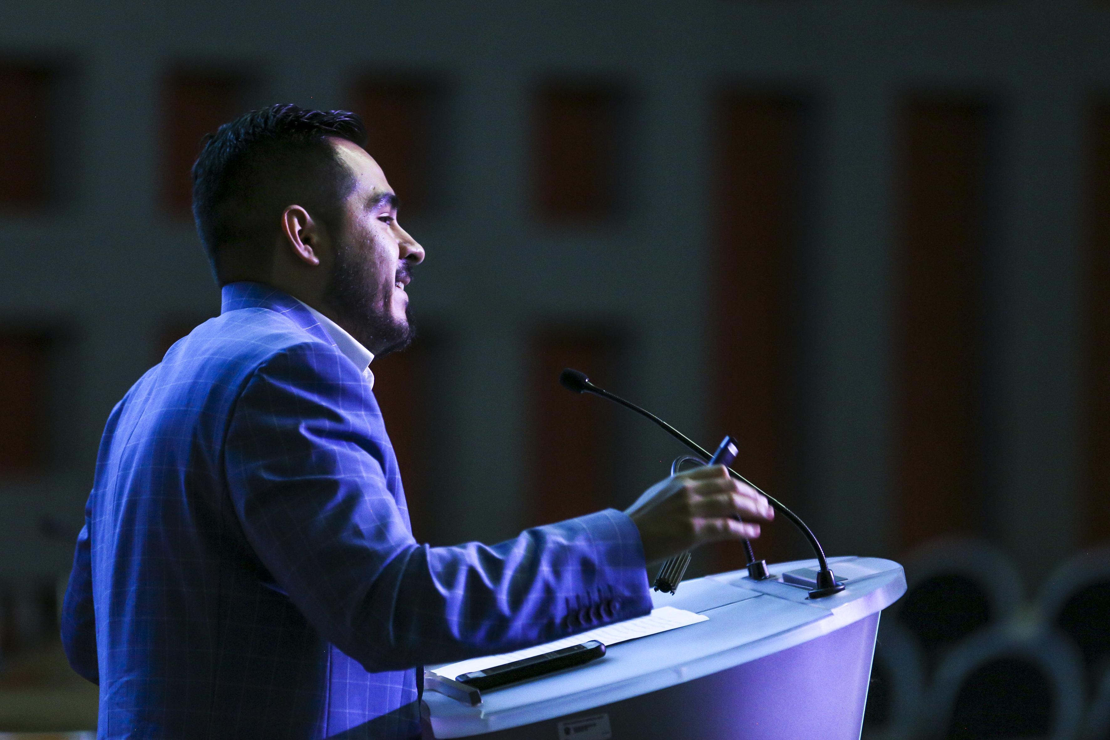Conferencista en podium, toma de perfil