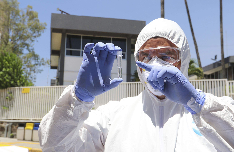 Médico del CUCS con traje de protección y guantes revisando un tubo de ensayo en el módulo de toma de pruebas en el estacionamiento
