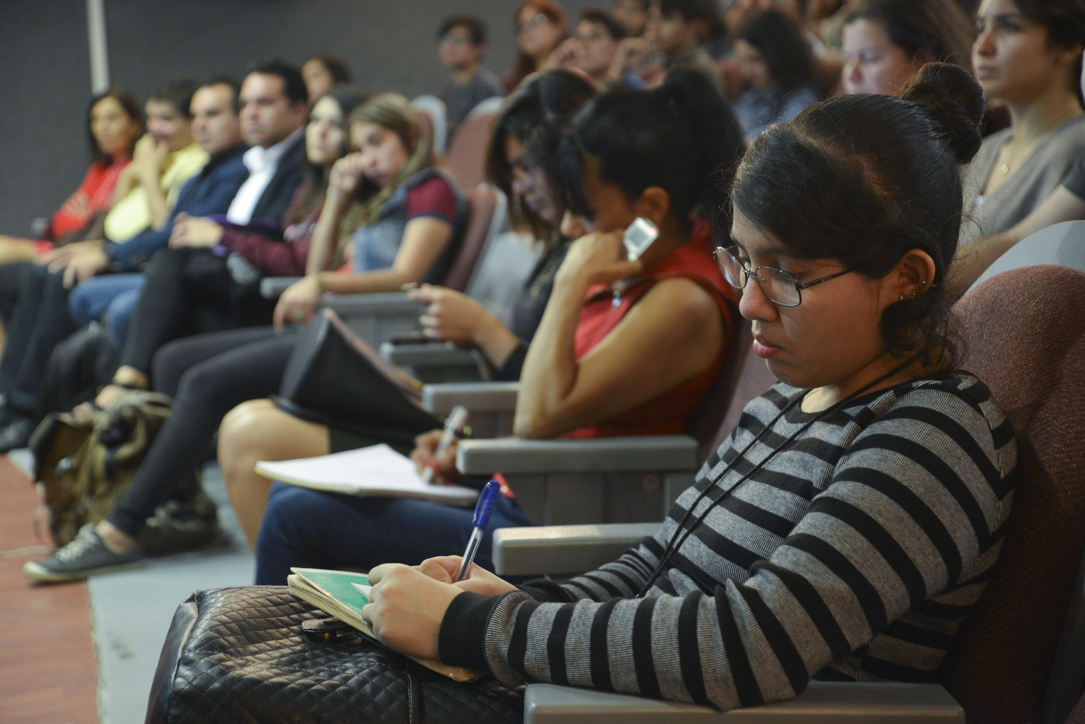 Alumnos asistentes a la conferencia tomando nota