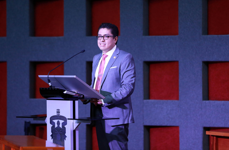 Dr. José Francisco Muñoz Valle ofreciendo discurso en el pódium, toma desde un costado del auditorio