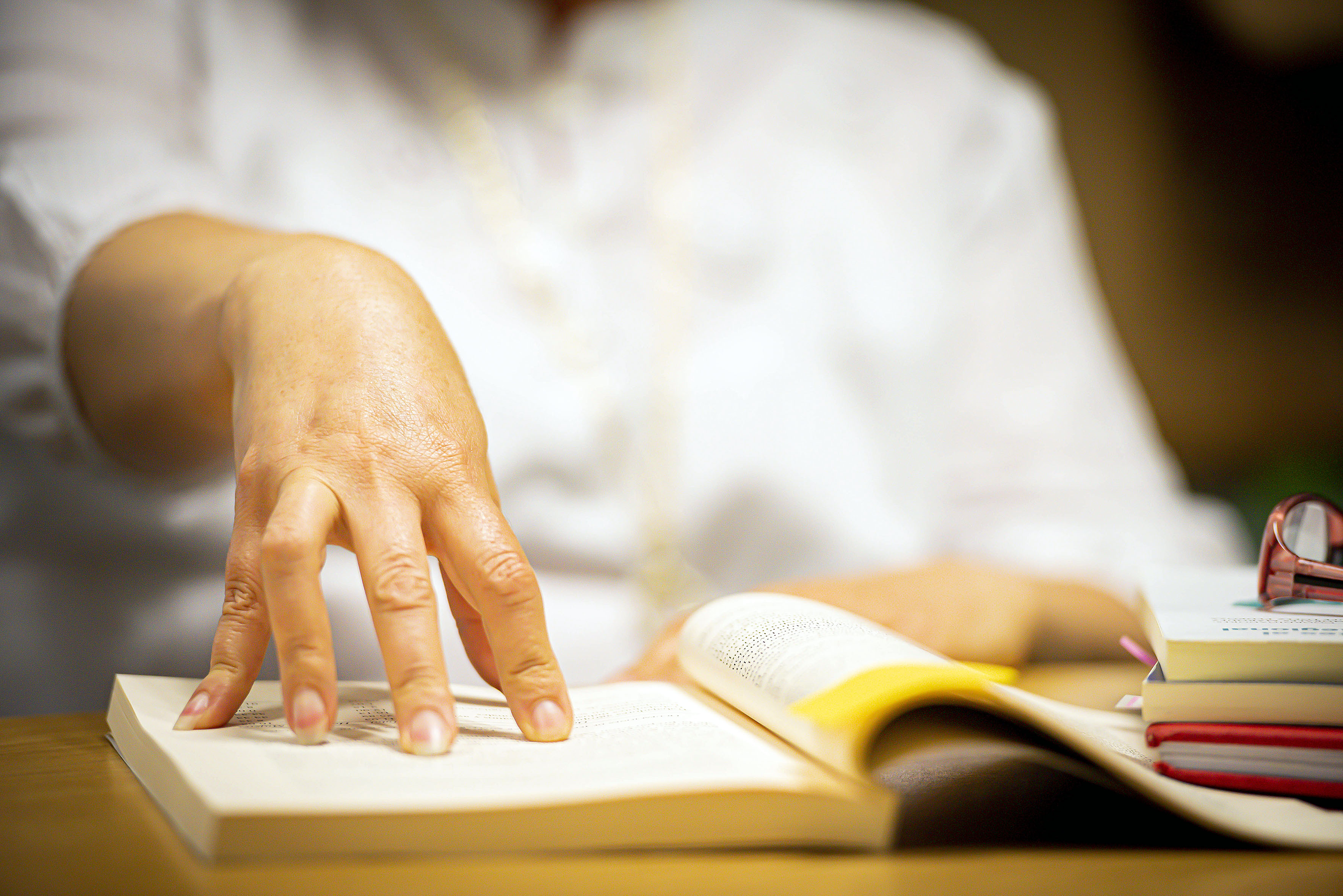 Mano femenina señalando un libro