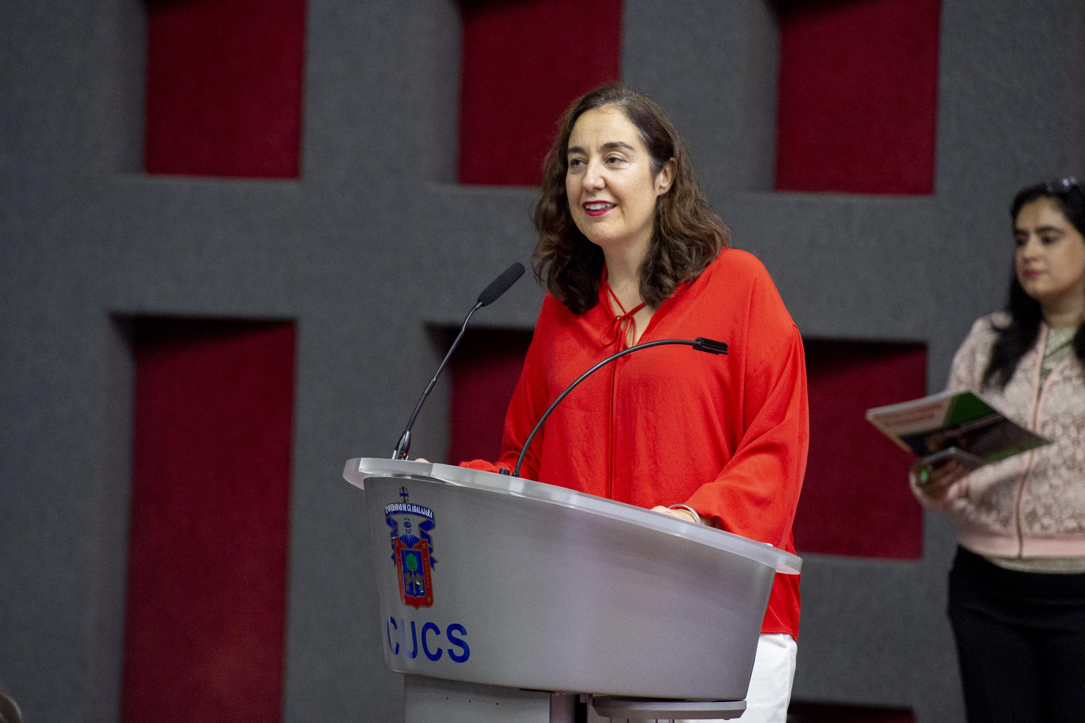 Dra Bárbara Vizmanos al micrófono en el podio