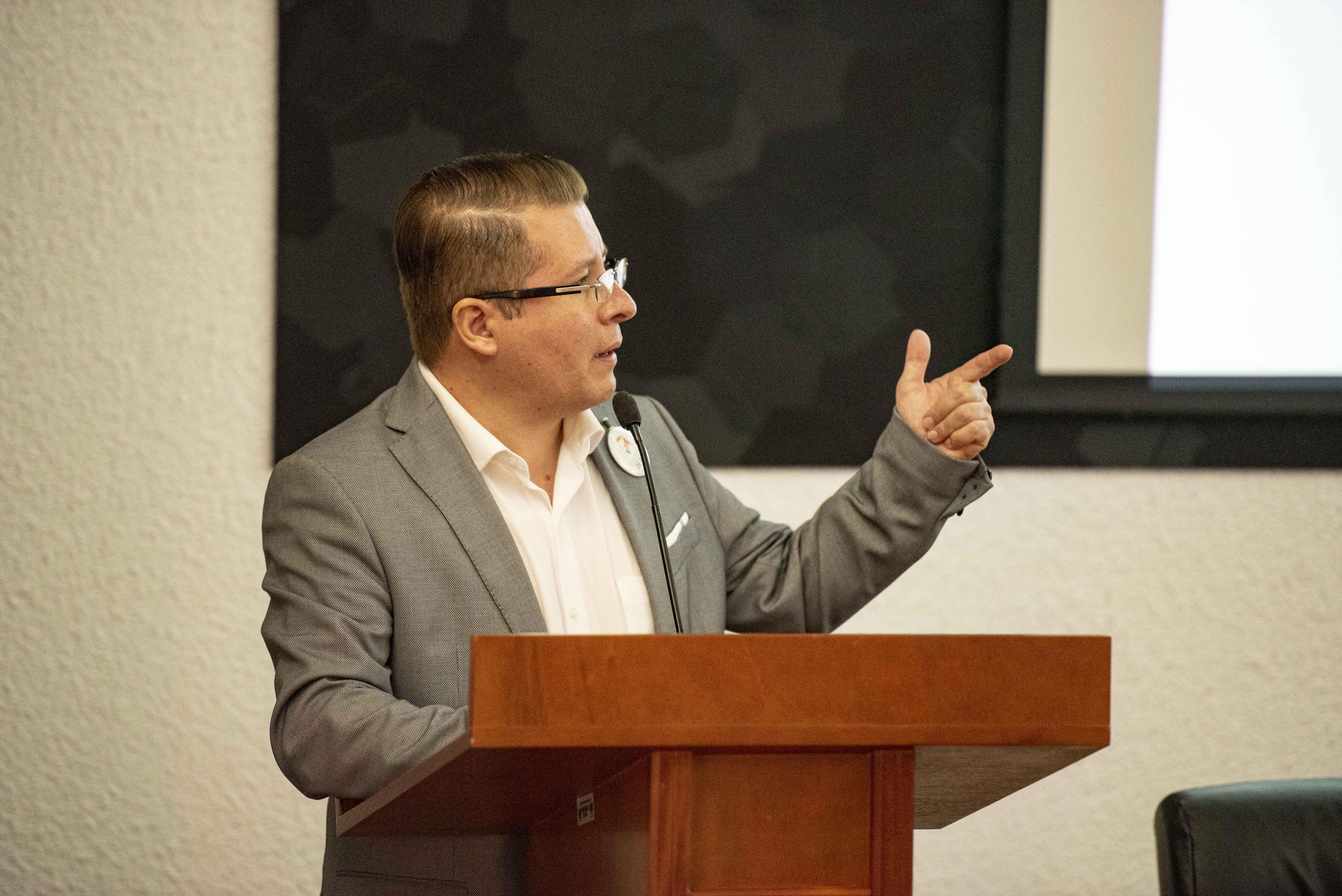 Defensor de los Derechos Universitarios ofreciendo conferencia en pódium