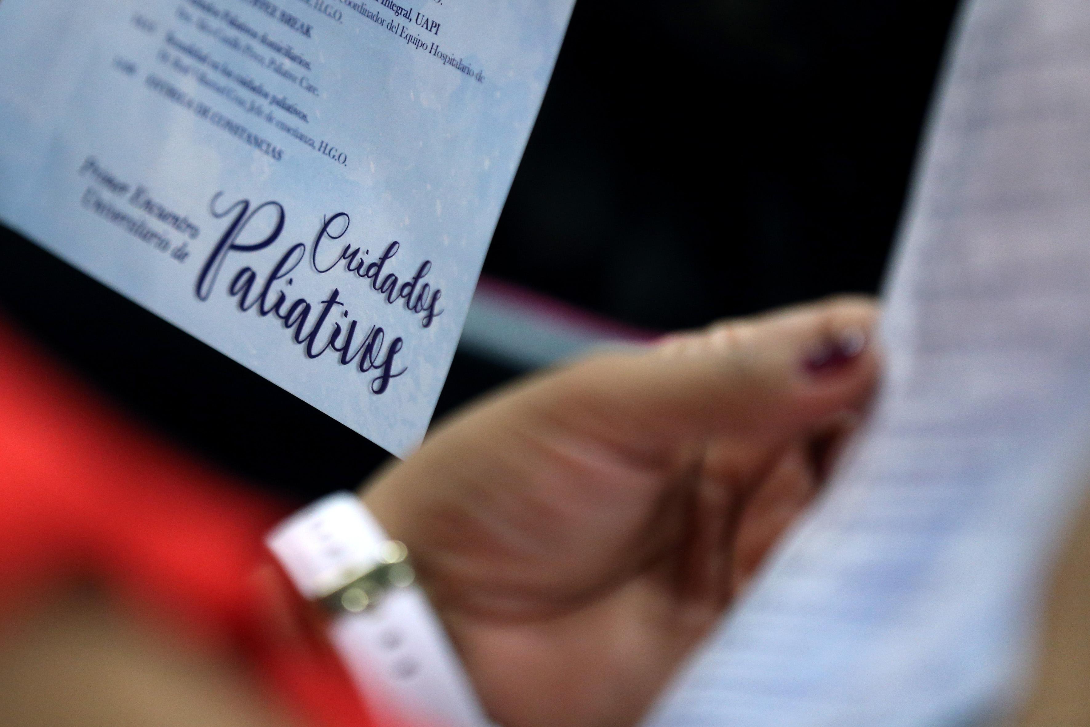 Imagen del díptico publicitario del evento en las manos de un asistente al Encuentro