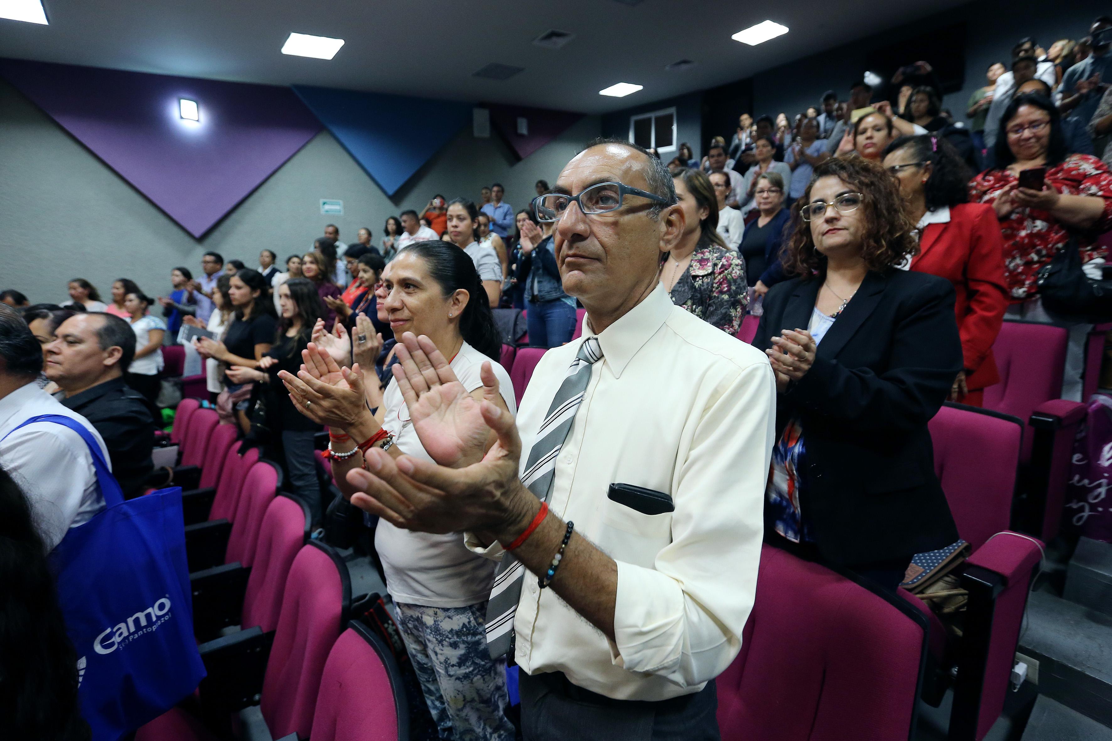 Asistentes de pie aplaudiendo tras el acto inaugural