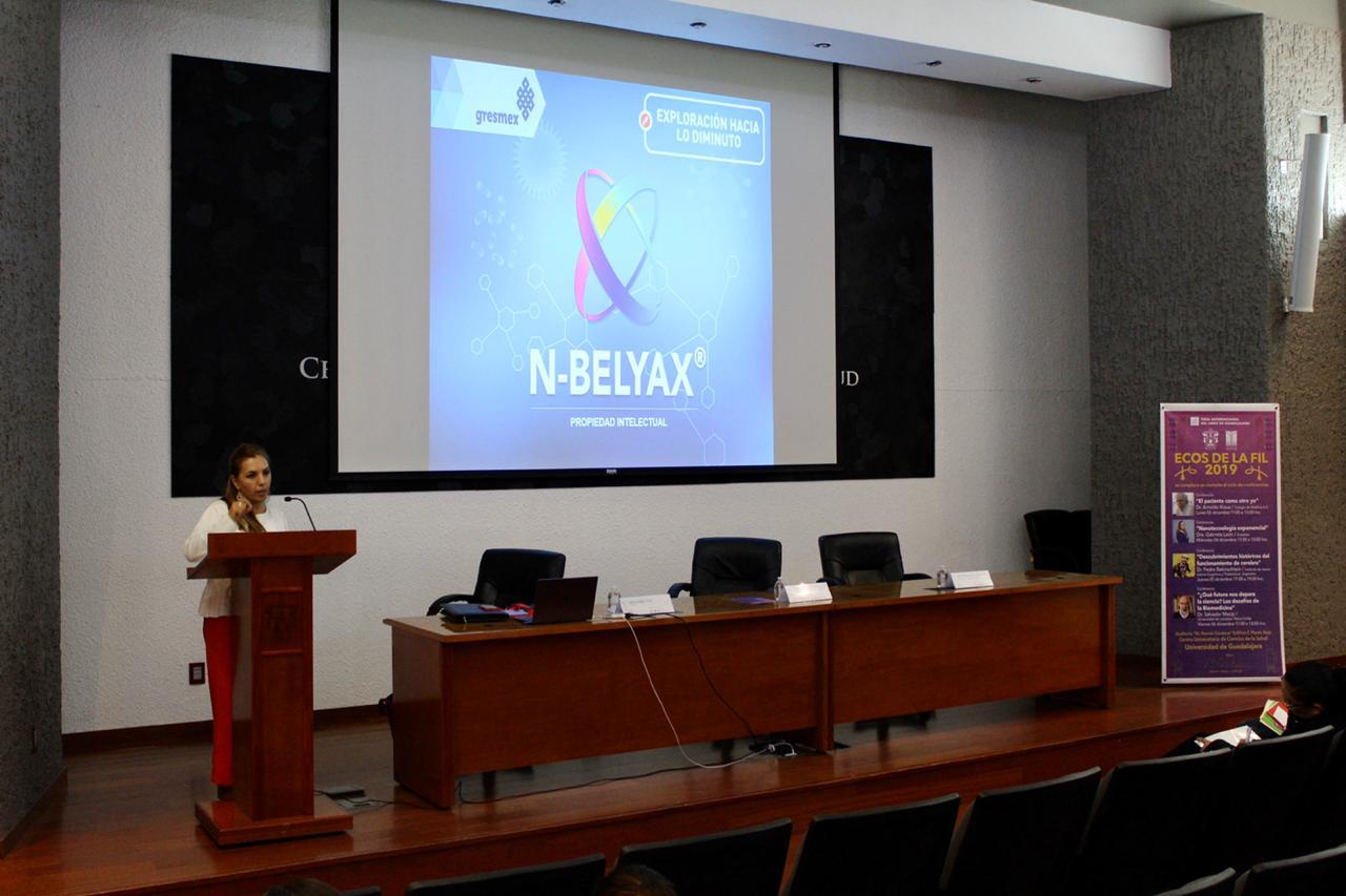 Toma desde atrás, al frente la ponente exponiendo una diapositiva
