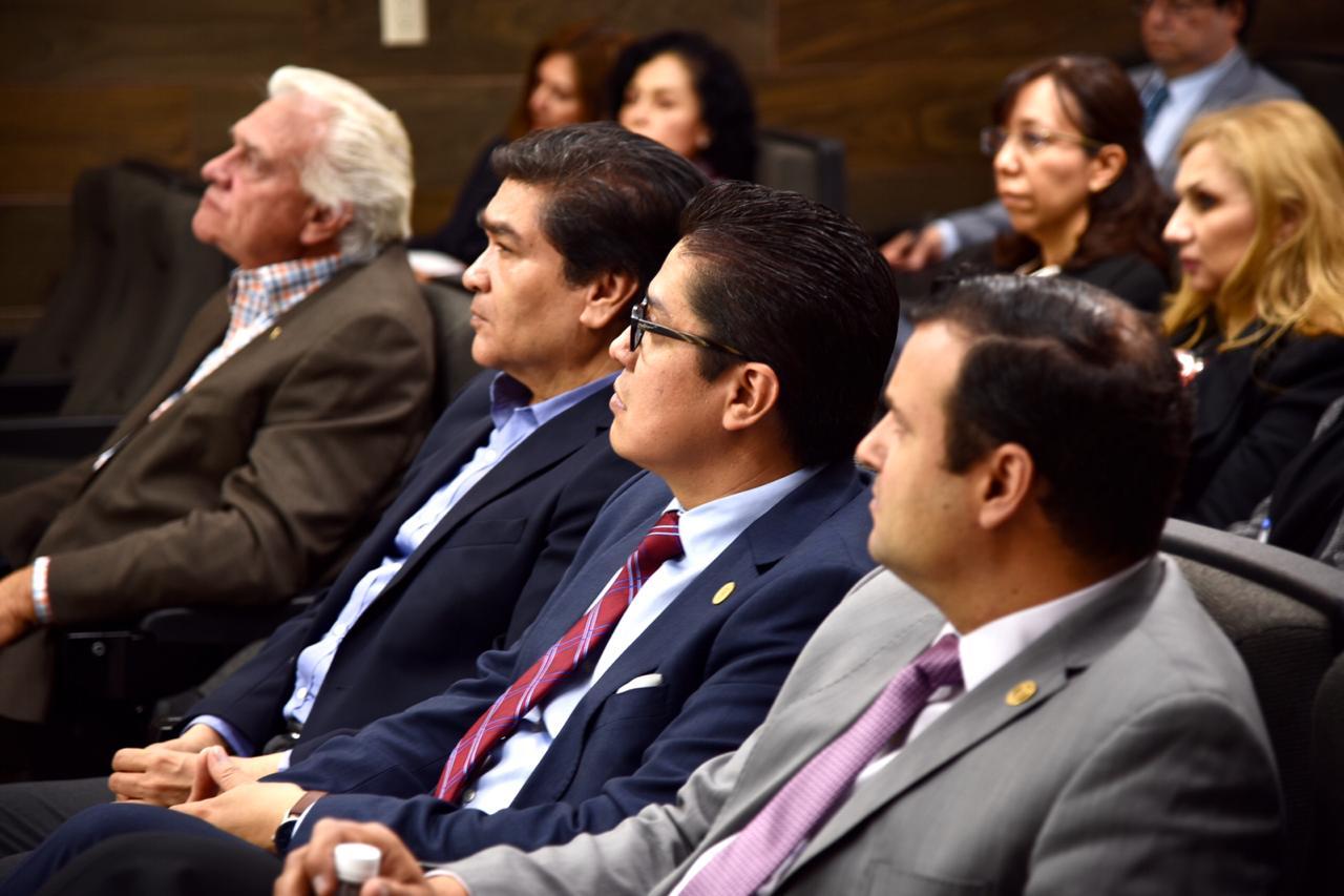 Autoridades del CUCS sentados en butacas escuchando al coordinador del programa educativo