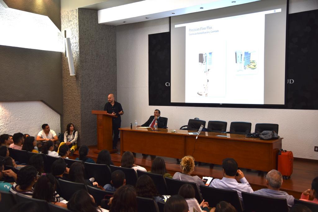 Toma desde atrás del auditorio, al fondo el ponente y una diapositiva en la pantalla