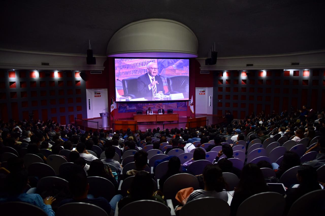 Toma abierta desde atrás del auditorio que luce lleno, al fondo en la pantalla la imagen del conferencista