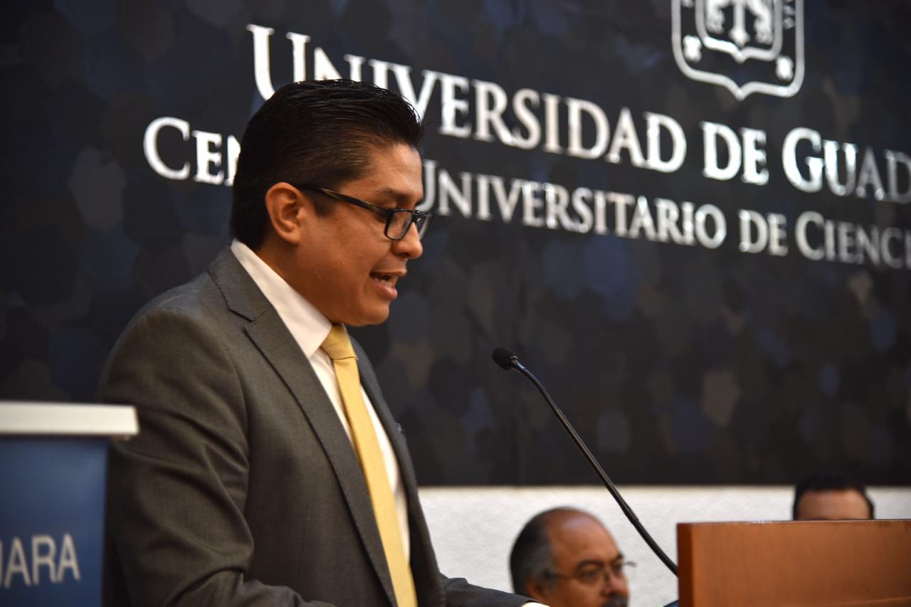 Al micrófono en el pódium el rector del CUCS
