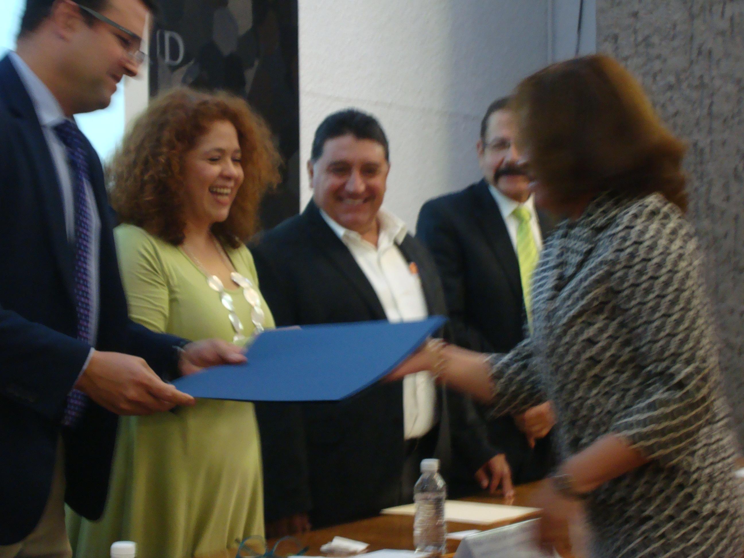 Secretario Académico entregando reconocimiento a una profesora