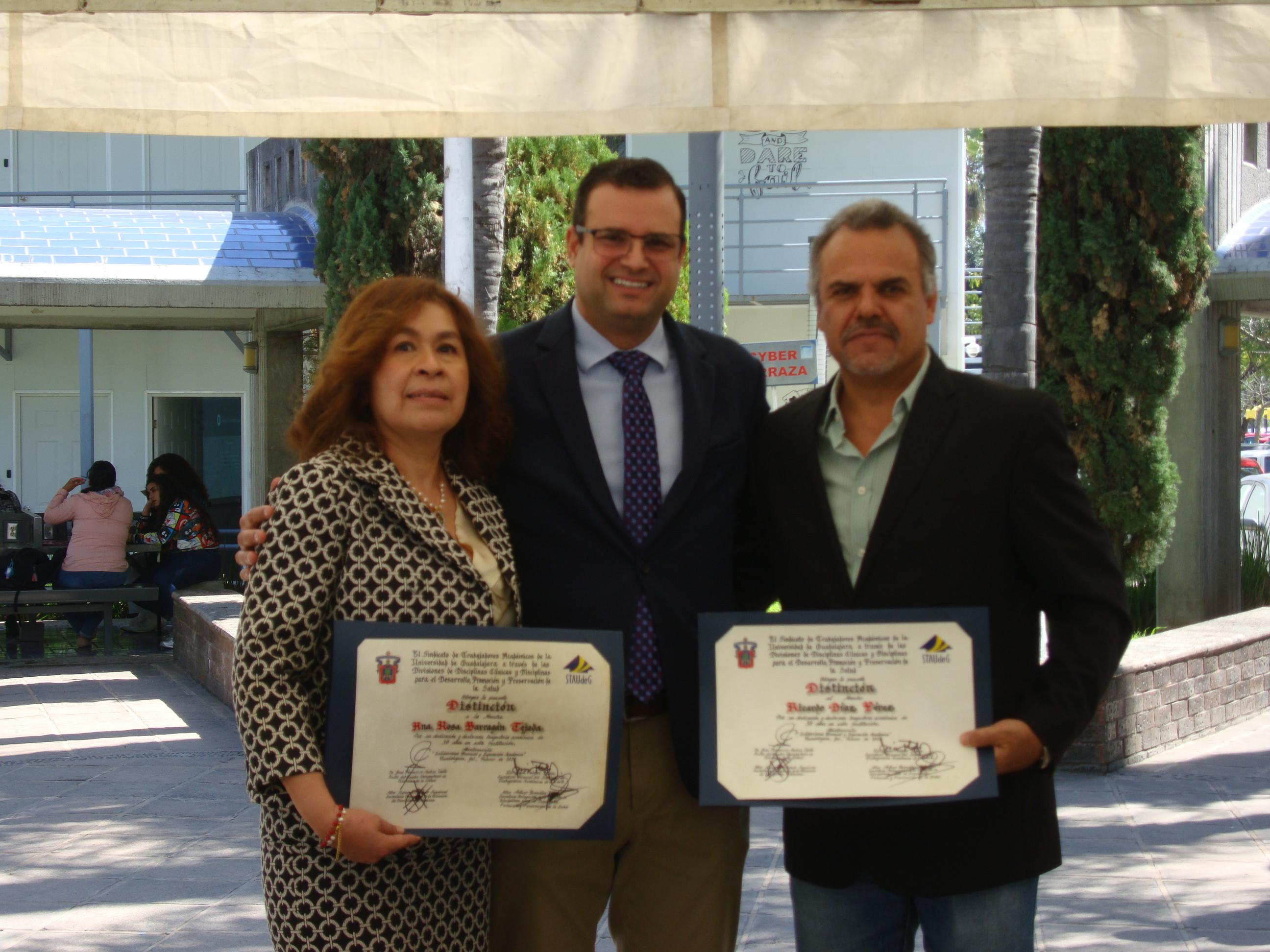 Profesores reconocidos con el secretario Académico exhibiendo su reconocimiento
