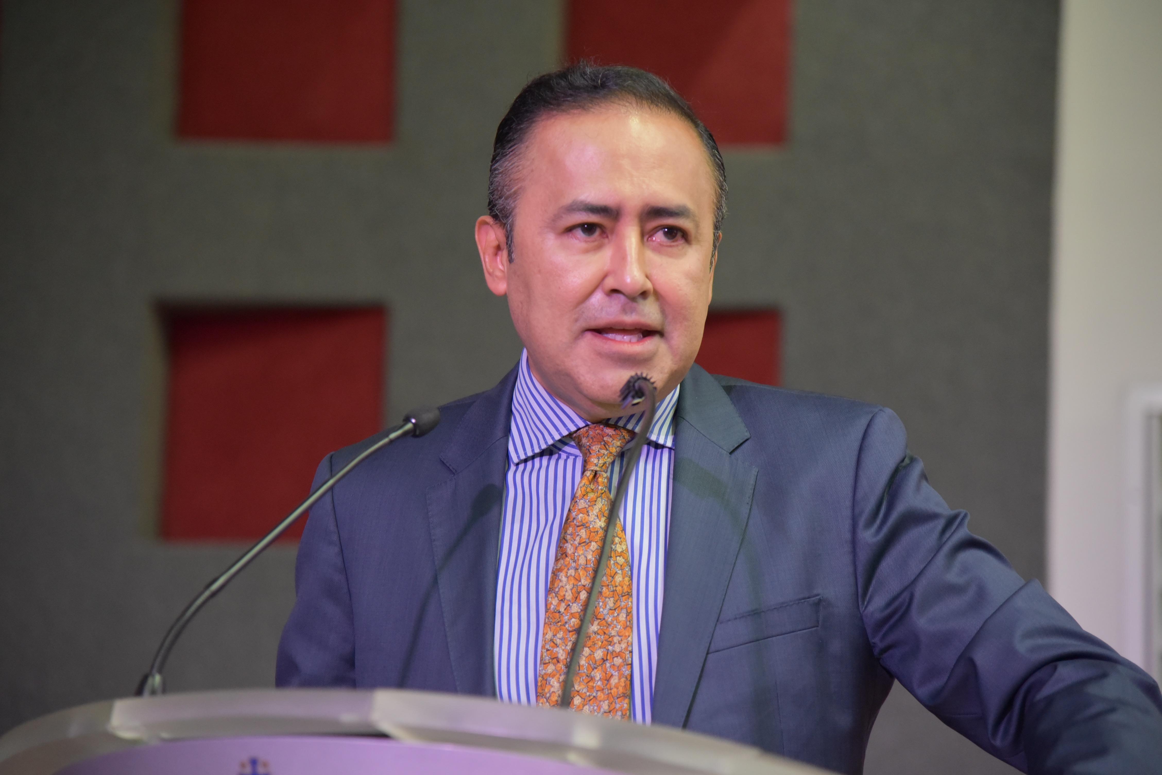 Dr. Jaime Andrade Villanueva ofreciendo discurso inaugural en podio