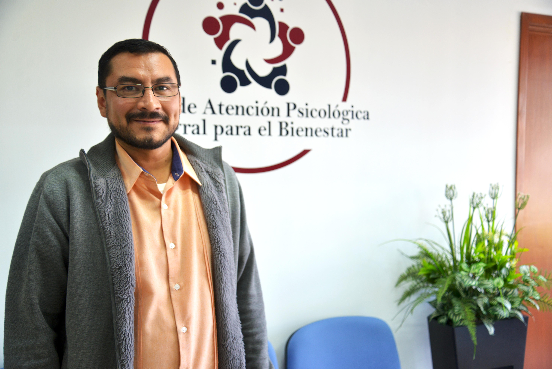 Dr. Rubén Bravo posando para la foto. Atrás logotipo de la Clínica de Atención Psicológica Integral para el Bienestar
