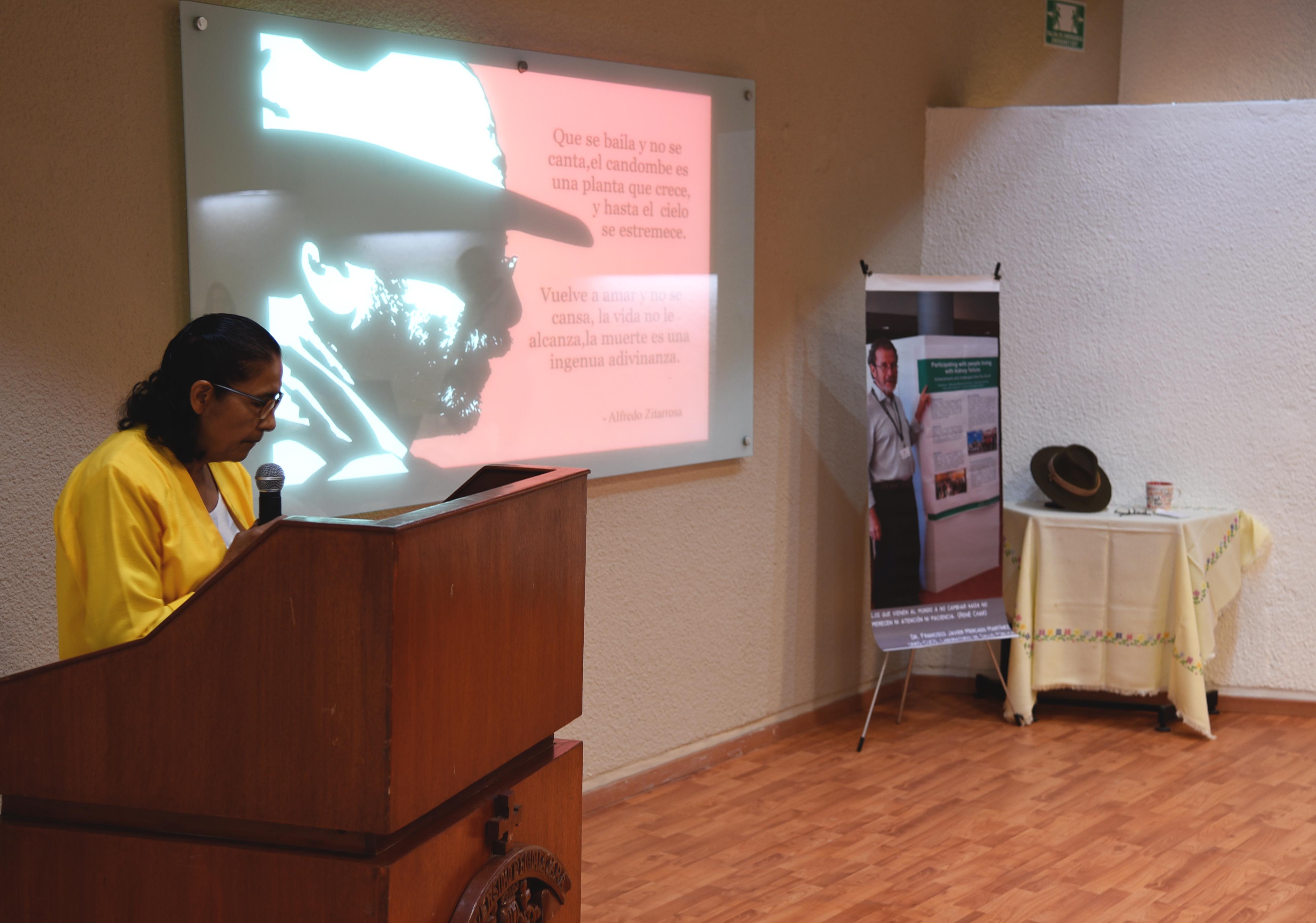Dra. Amparo Tapia en pódium. Al fondo foto de perfil y pertenencias del Dr. Mercado