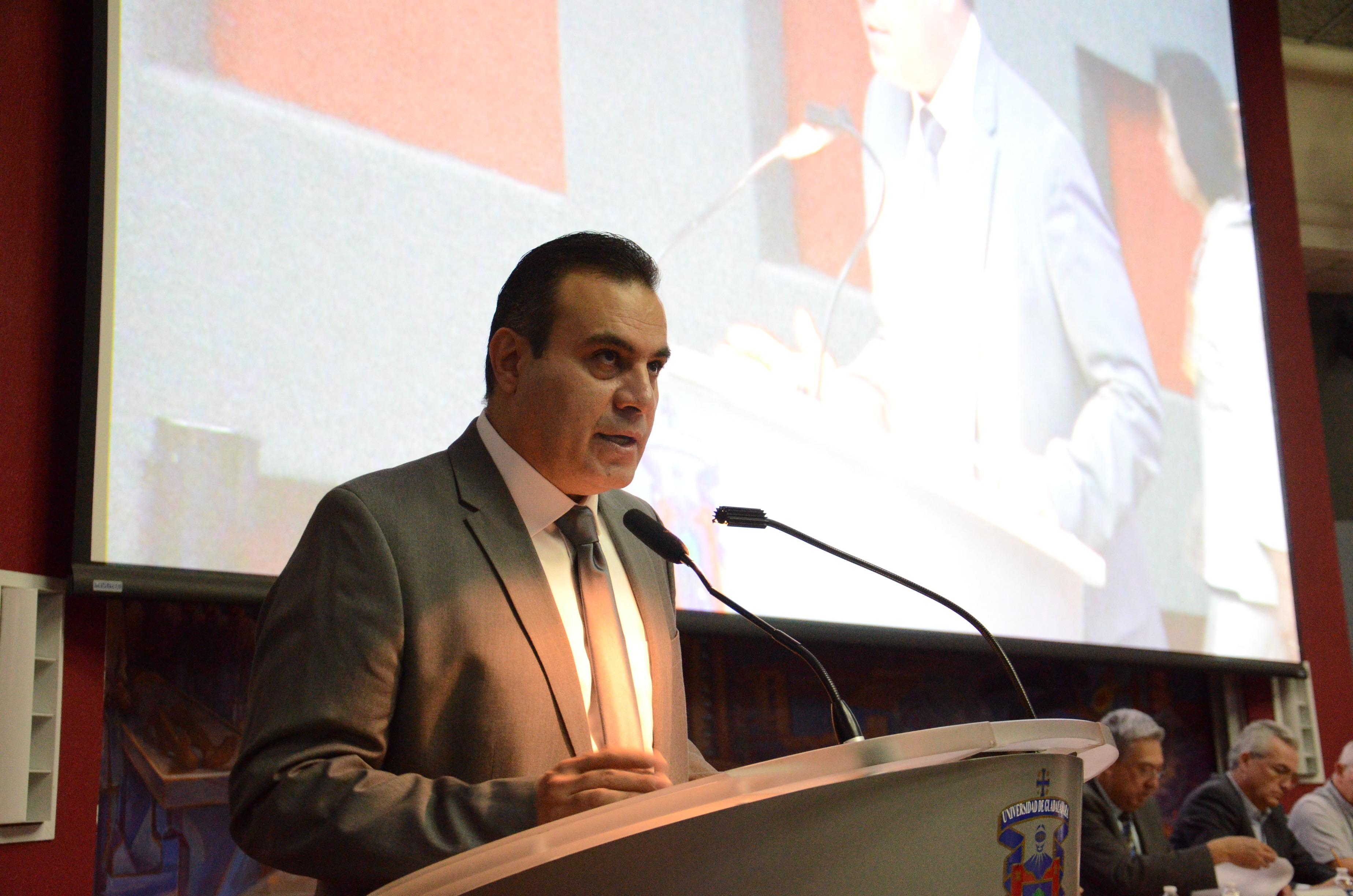 Dr. Igor Ramos ofreciendo palabras de bienvenida en el pódium