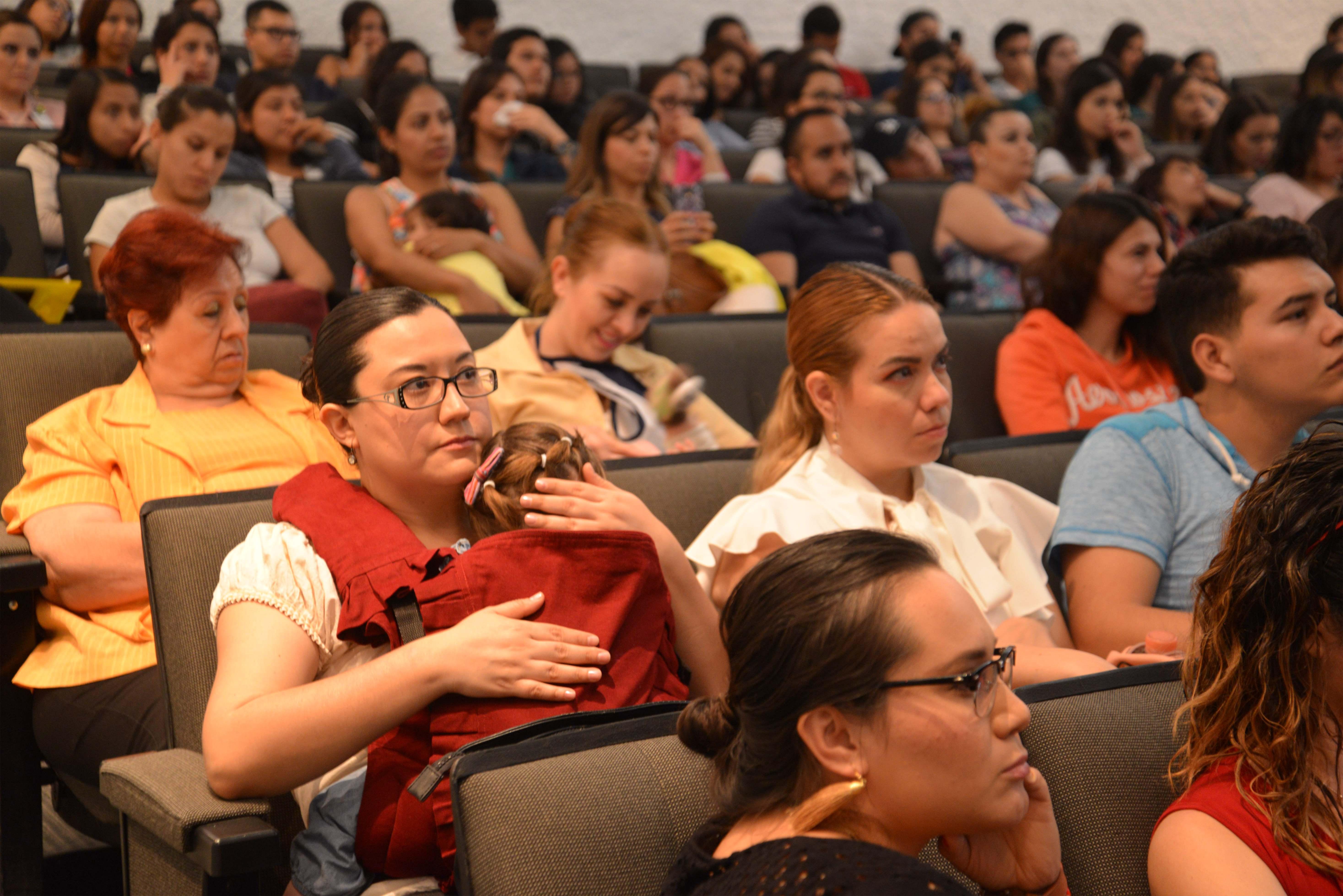 Mamá con su hija dormida en brazos escuchando la conferencia