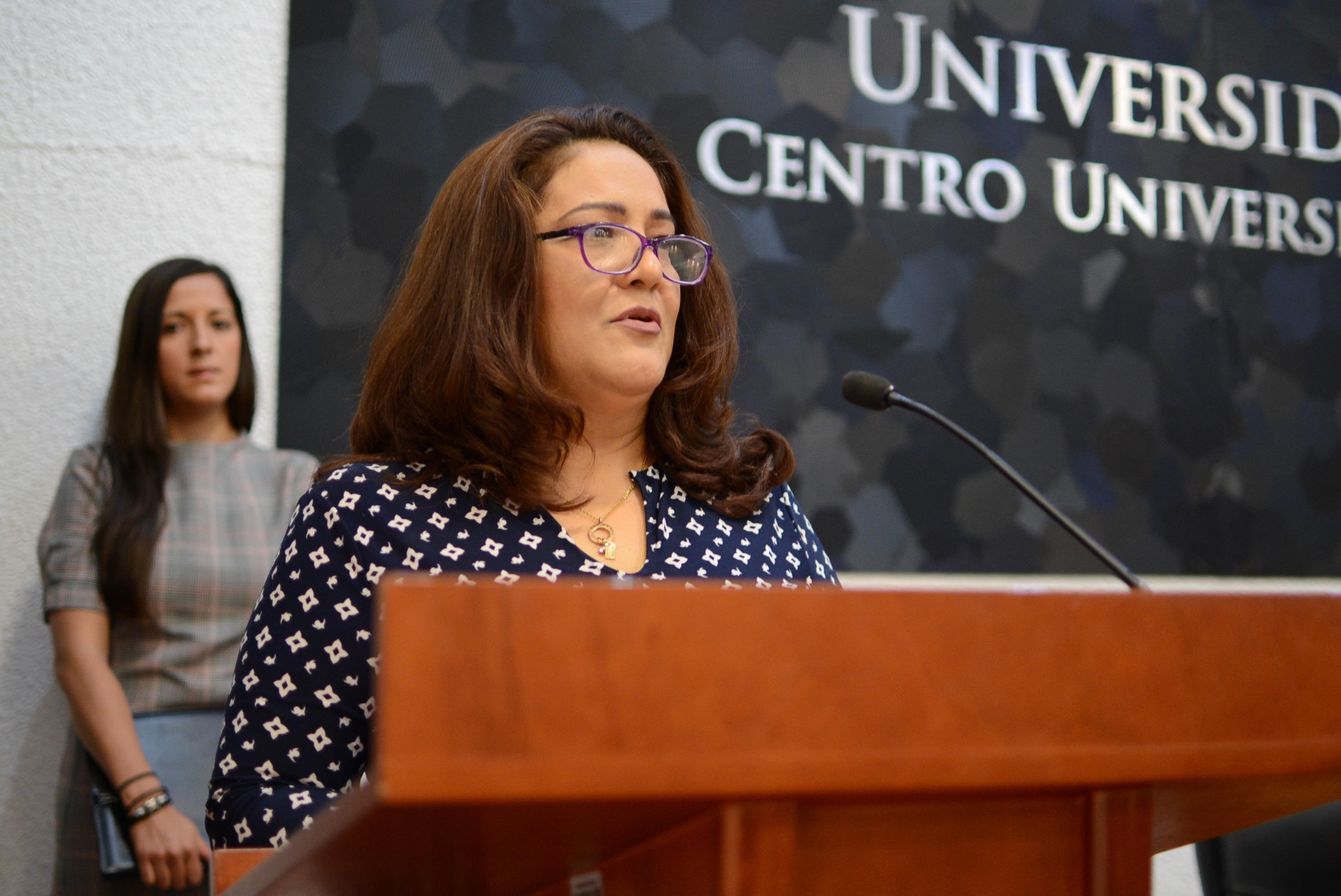 Lic. María Dolores Villegas, representante de los galardonados, ofreciendo mensaje en pódium