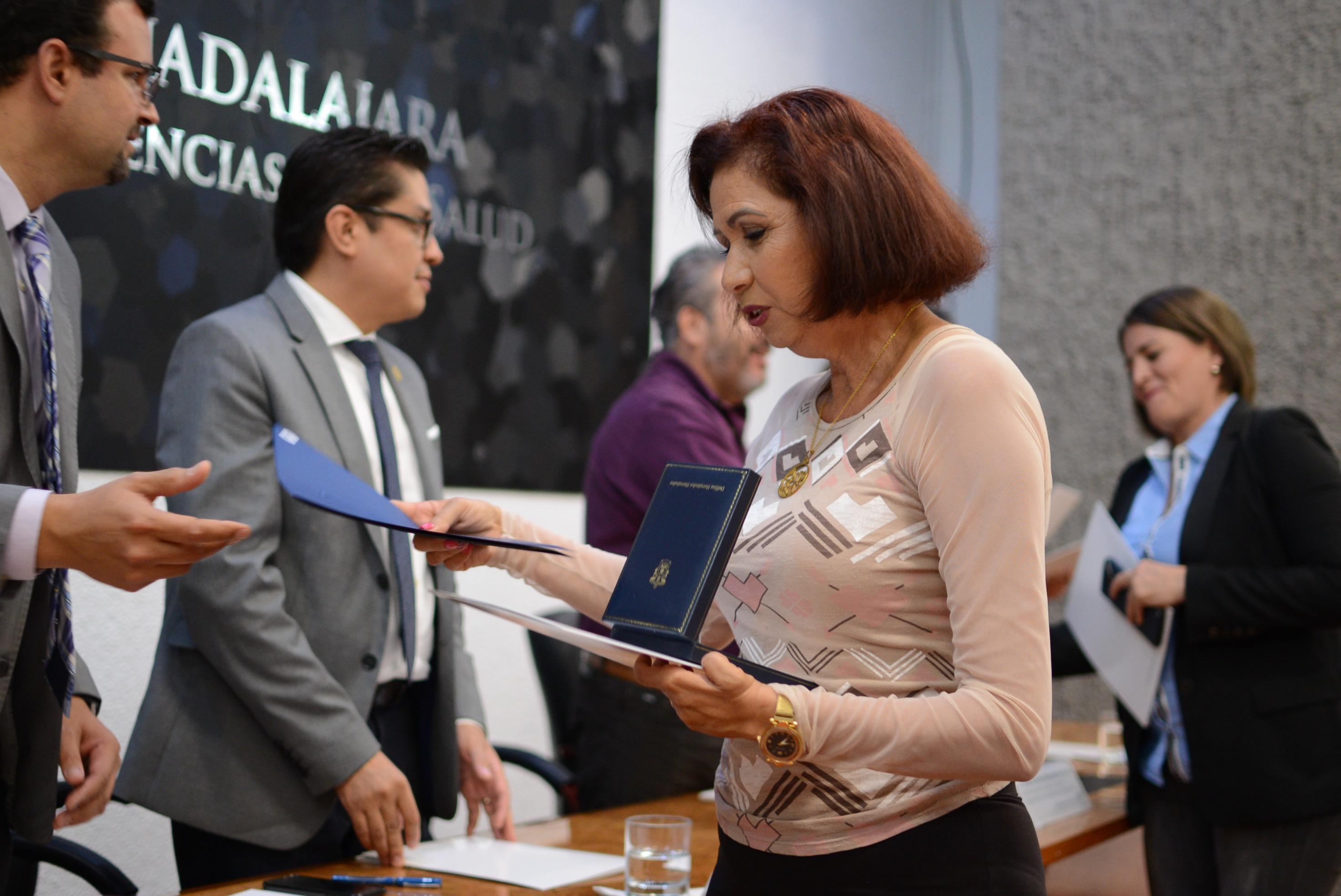 Trabajadora administrativa de CUCS recibiendo reconocimiento