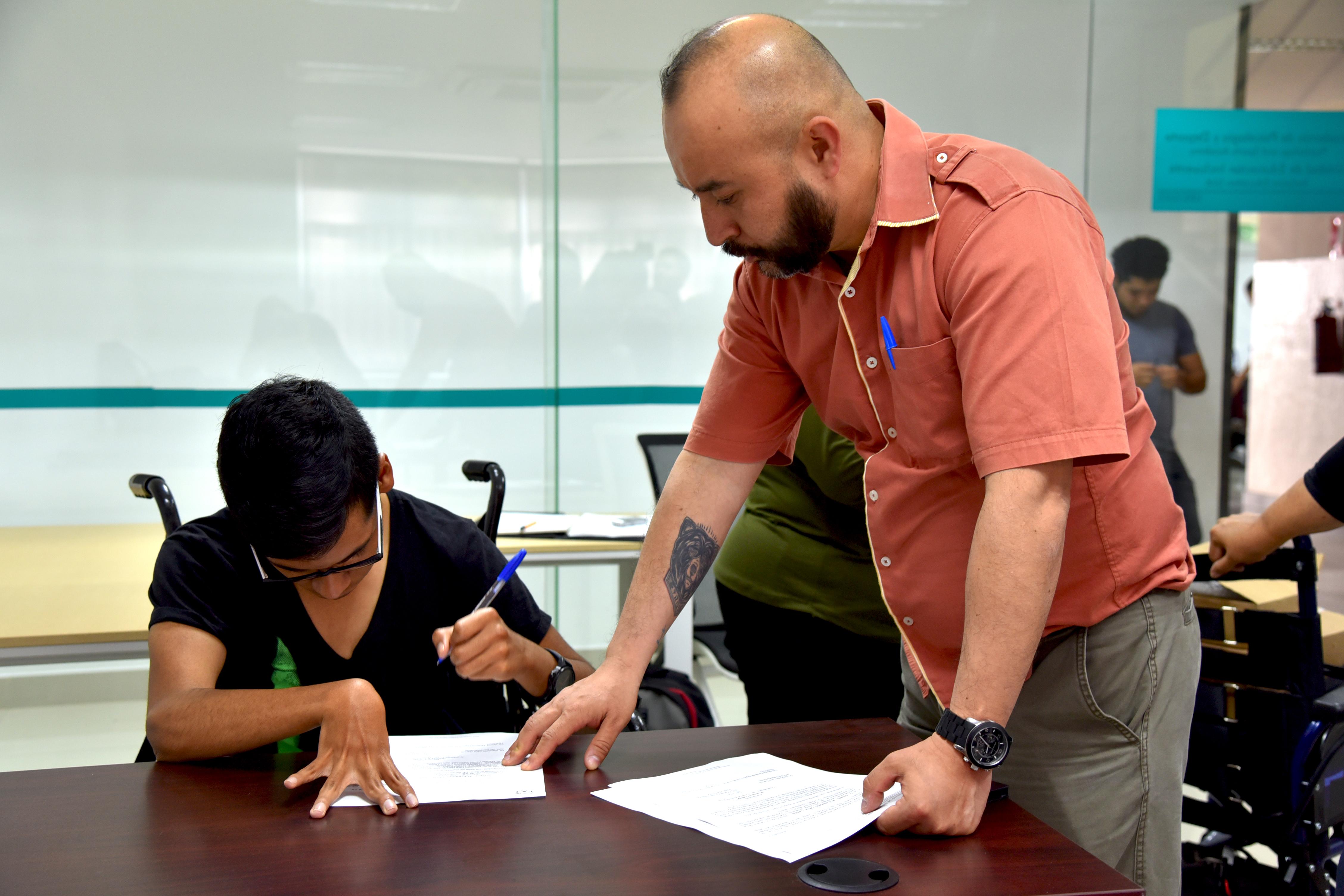 Daniel Cruz Alumno beneficiado firmando documentos
