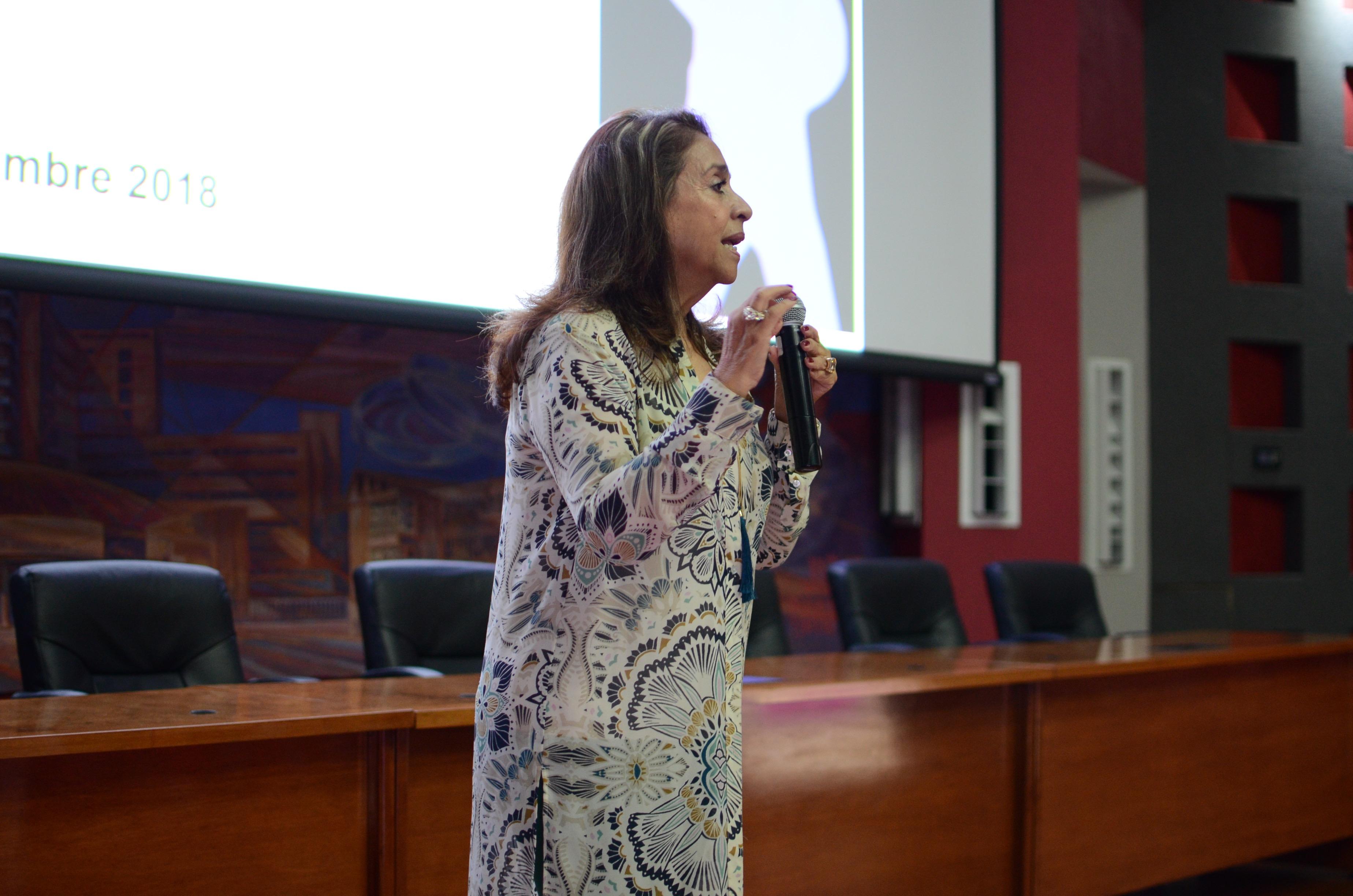 Dra. Norma Quezada al micrófono dando palabras de bienvenida