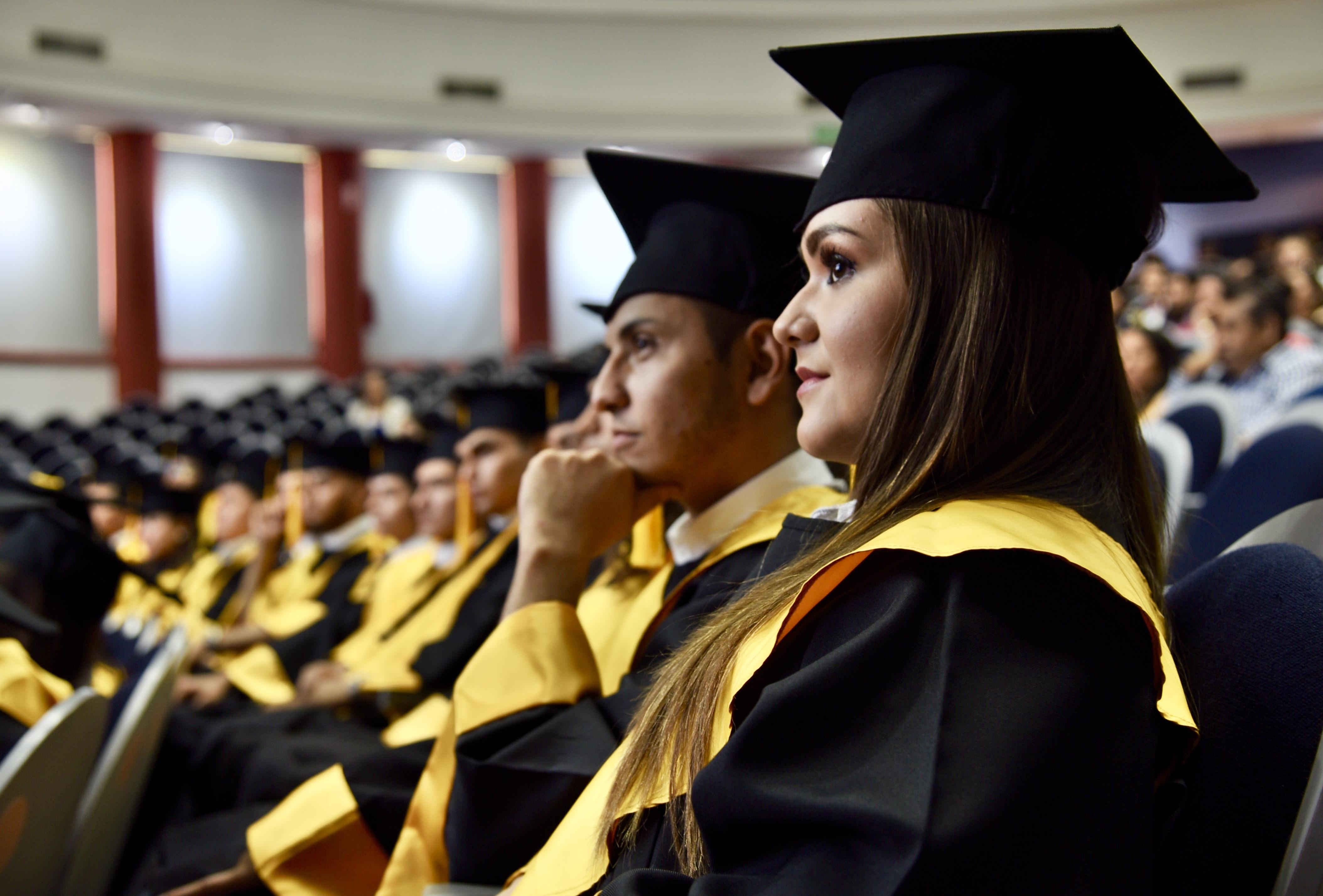 Graduados en el auditorio escuchando mensajes
