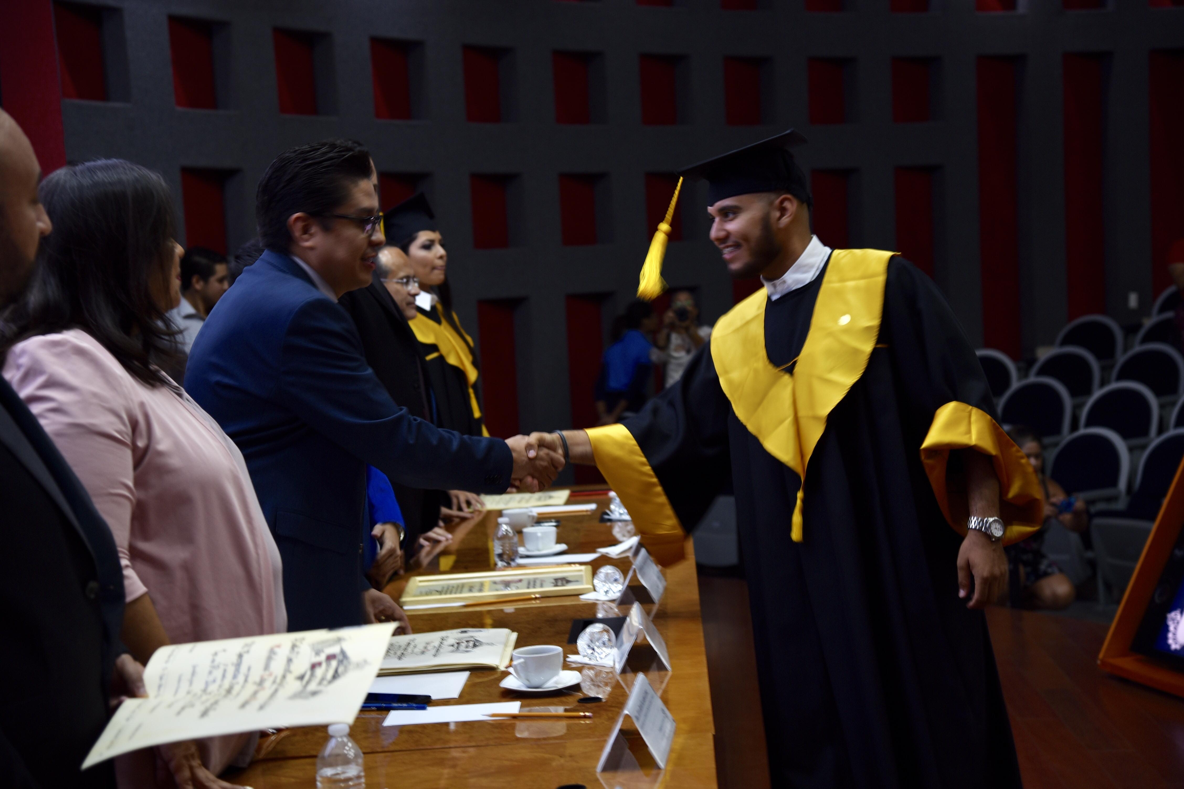 Rector CUCS entregando constancia a graduados