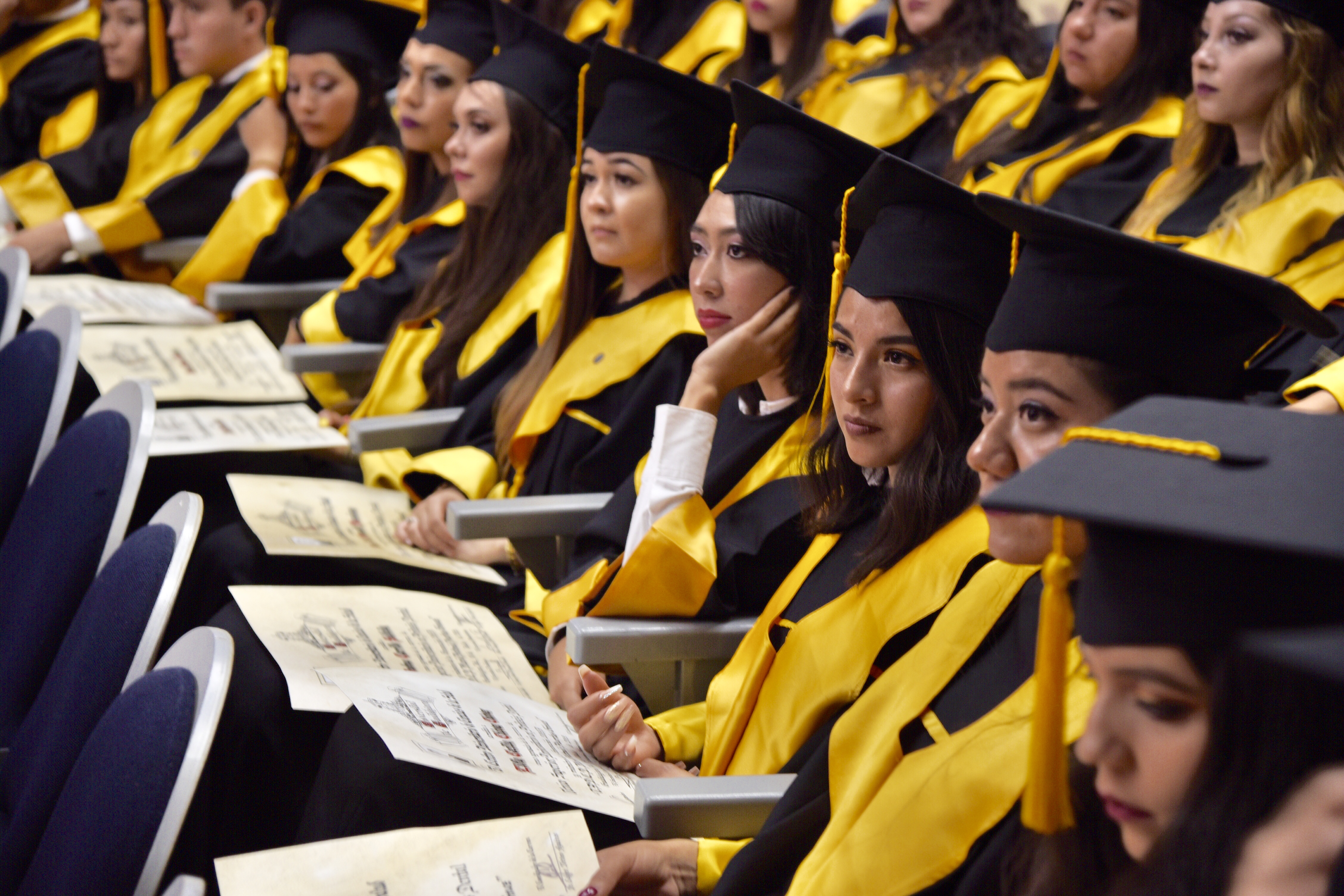 Foto de graduados sentados en sus butacas