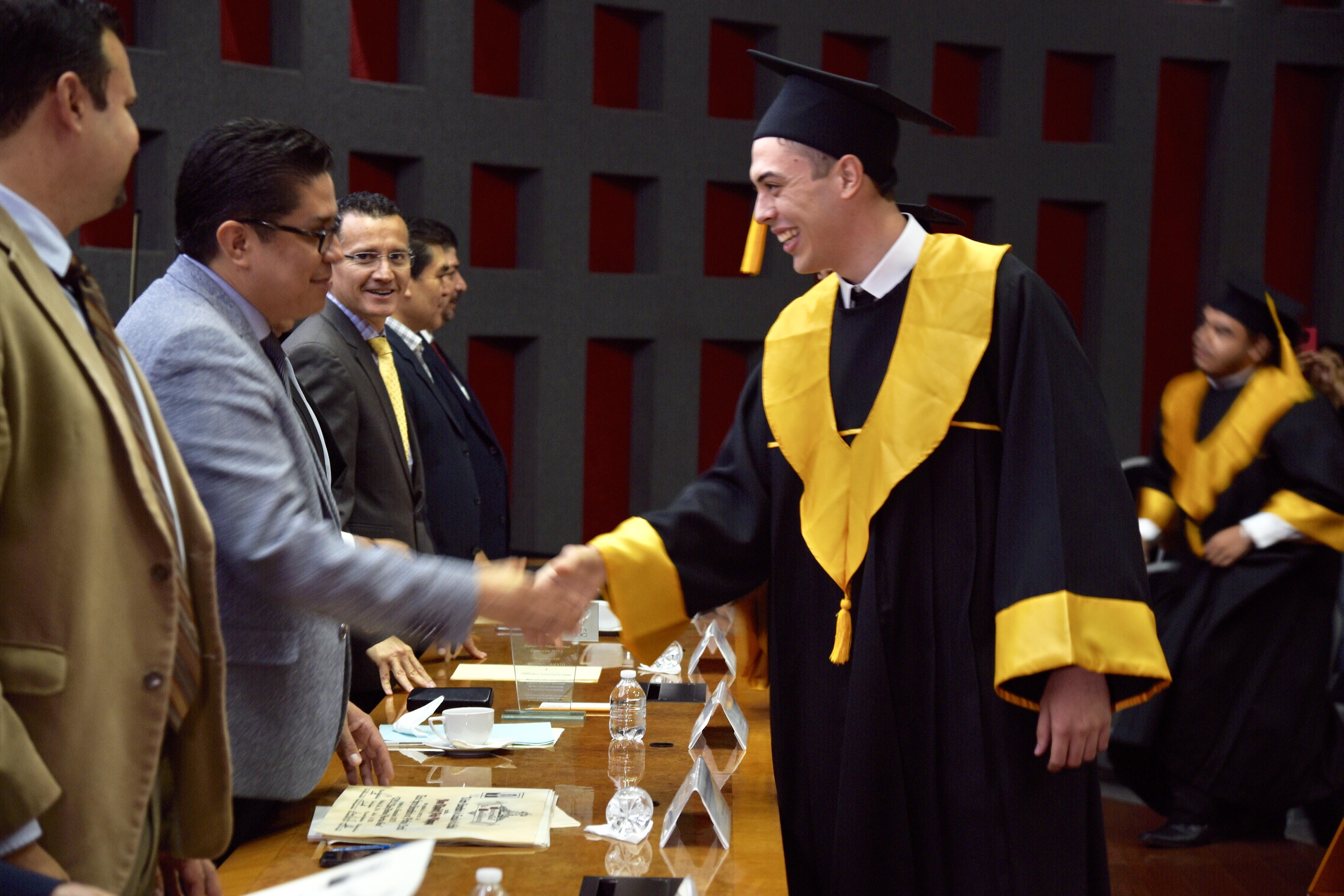 Rector del CUCS entregando constancia de egresado a graduado