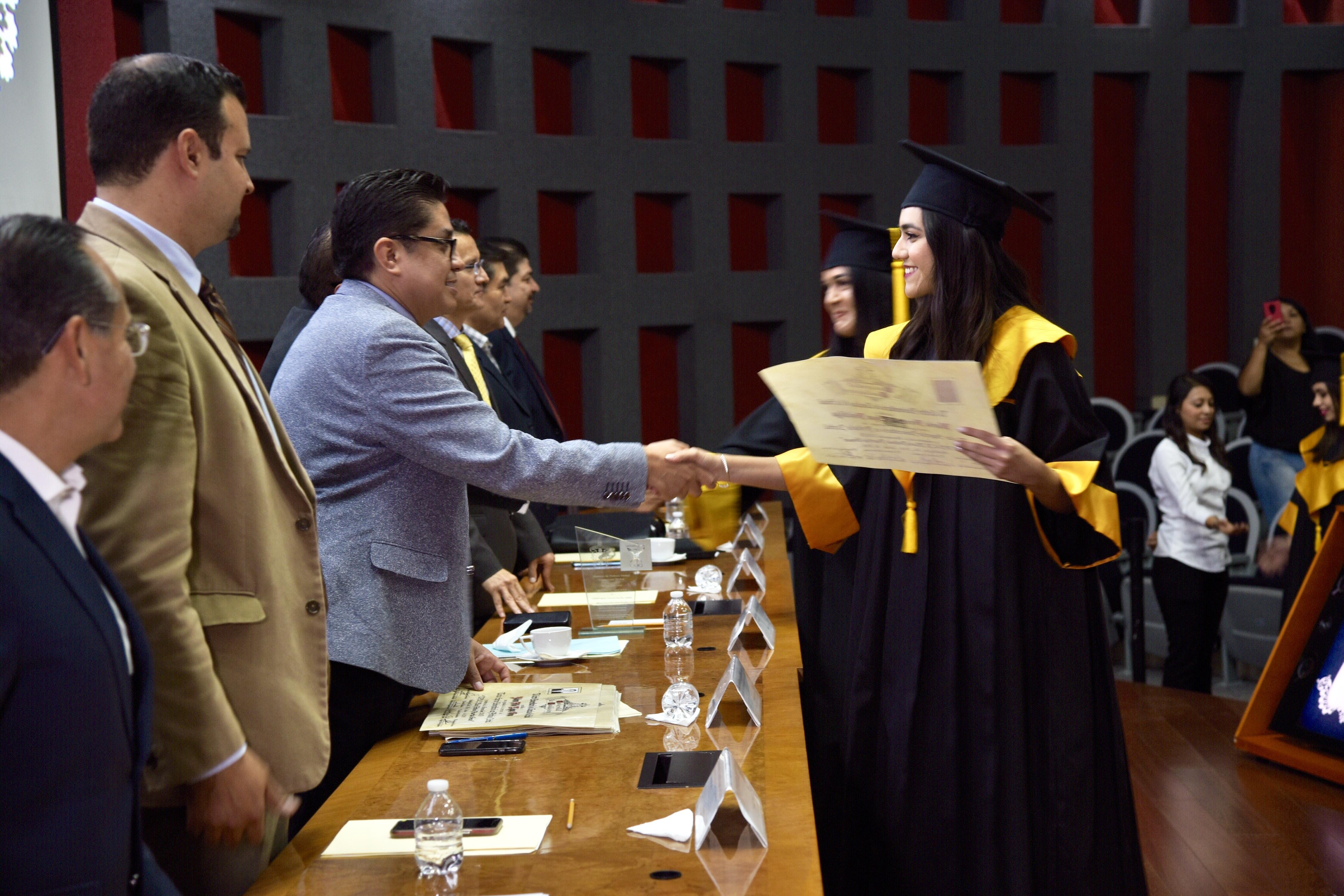 Rector del CUCS entregando constancia de egresado a graduada