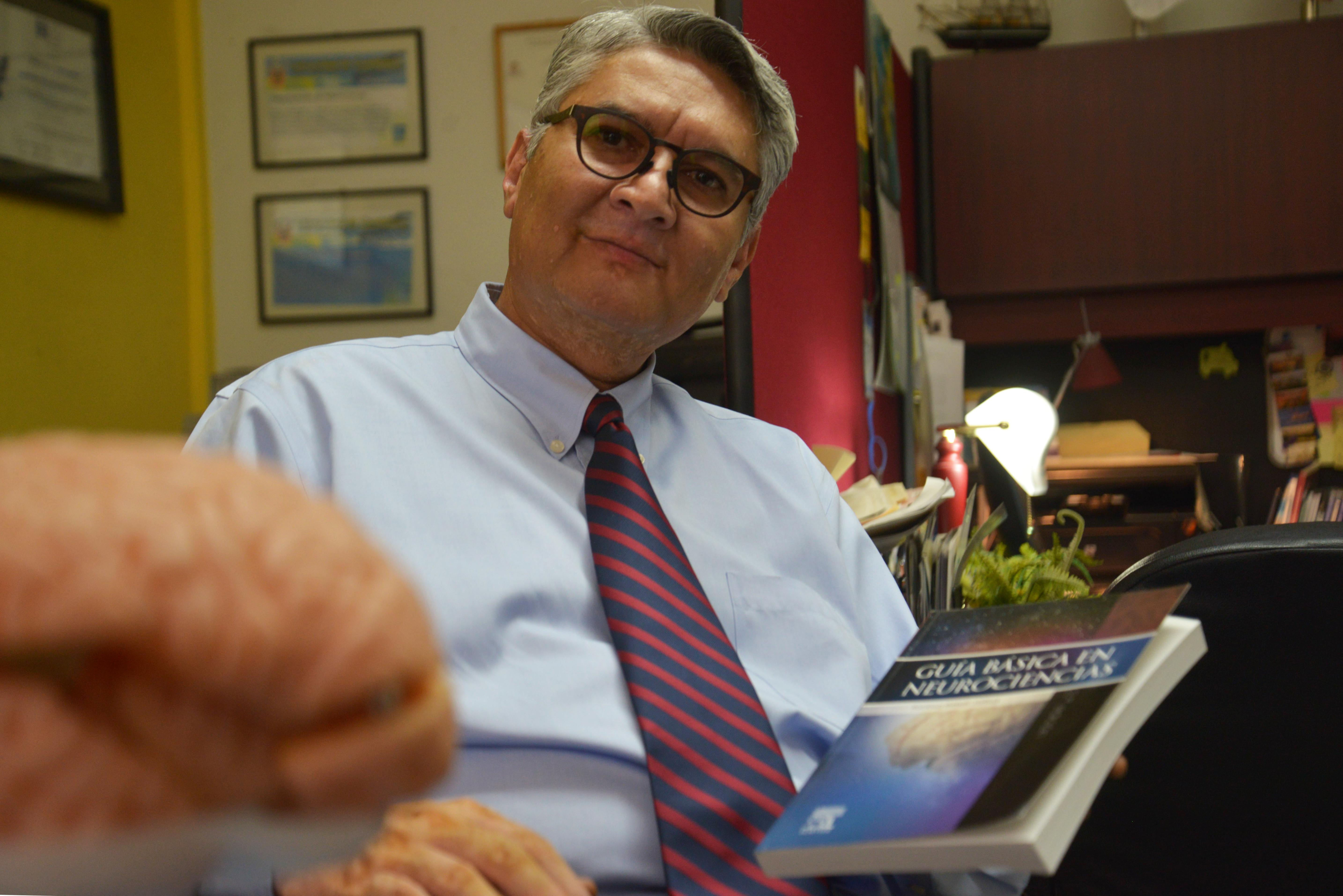 Dr. Rodrigo Ramos muestra el libro. En primer plano la réplica en silicón de un cerebro humano