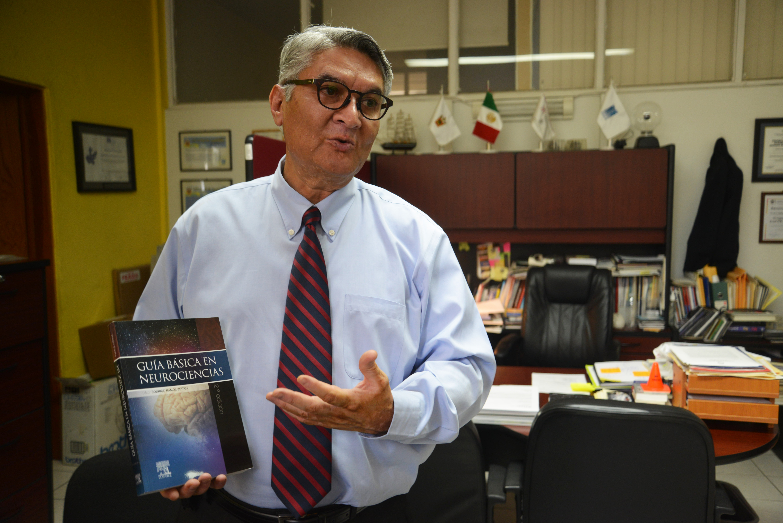 Dr. Rodrigo Ramos exhibe el libro durante la entrevista