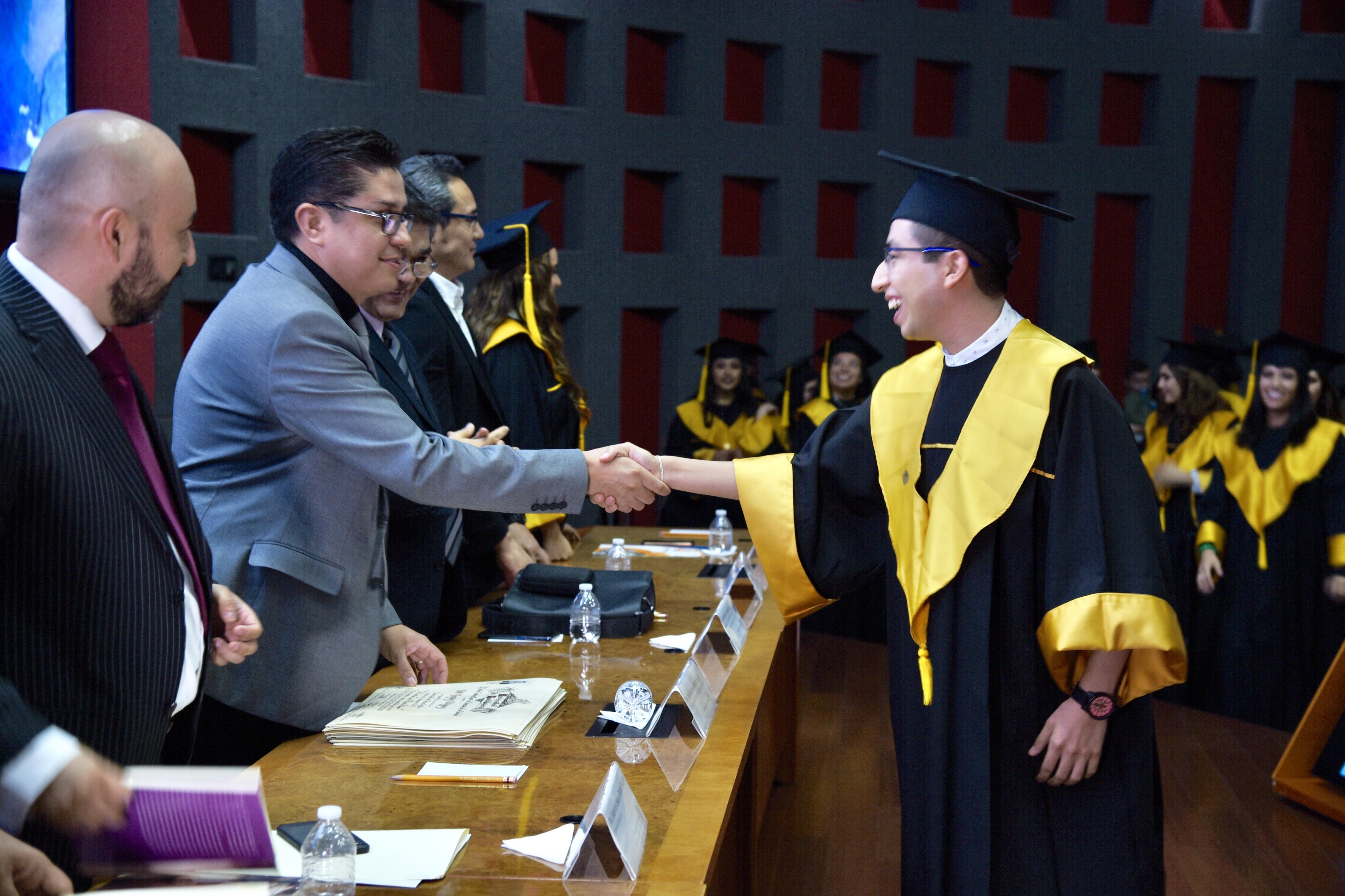 Rector entregando carta a graduado saludándolo de mano