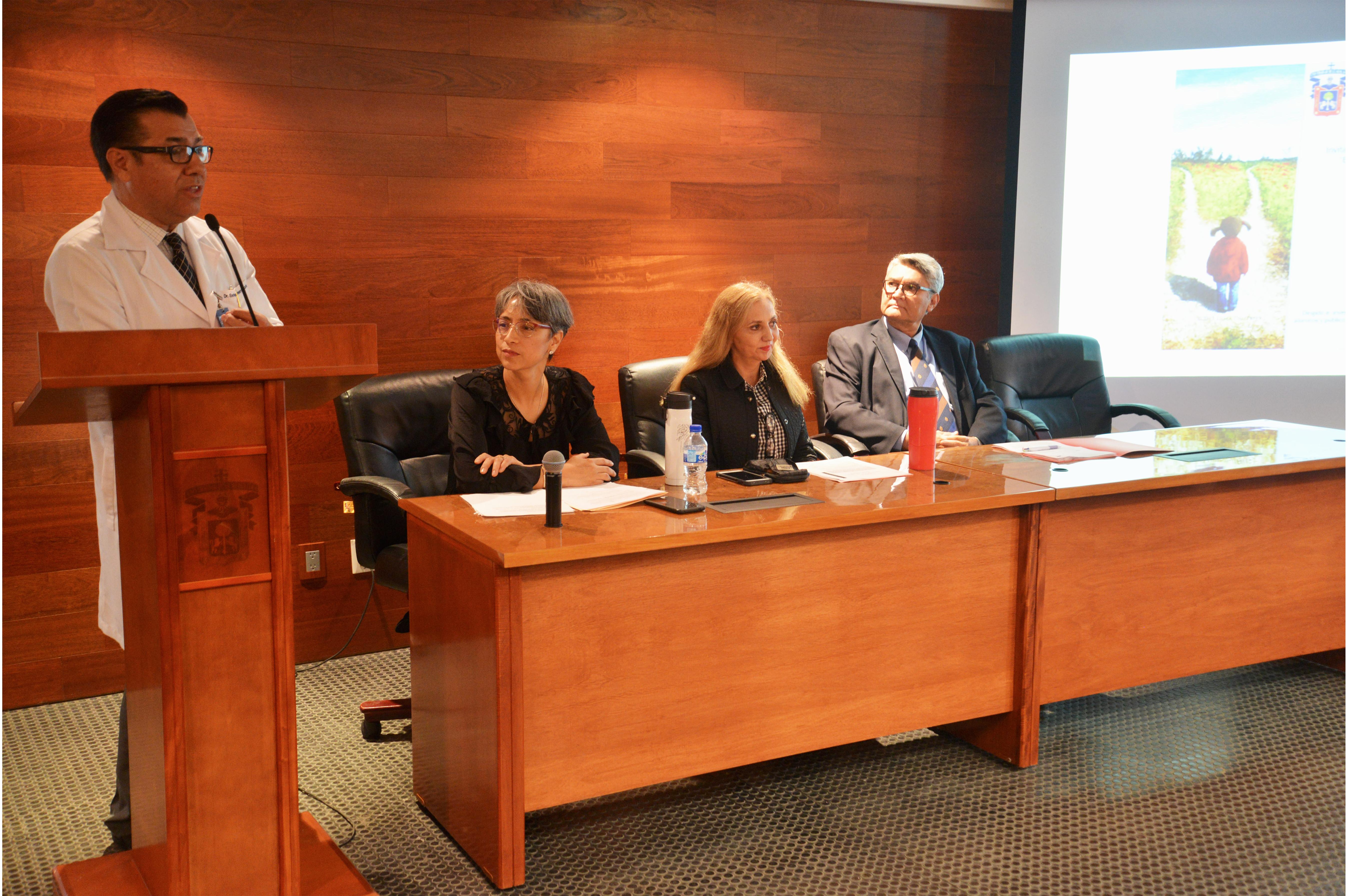 Dr. Enrique Velarde ofreciendo conferencia y miembros del presídium