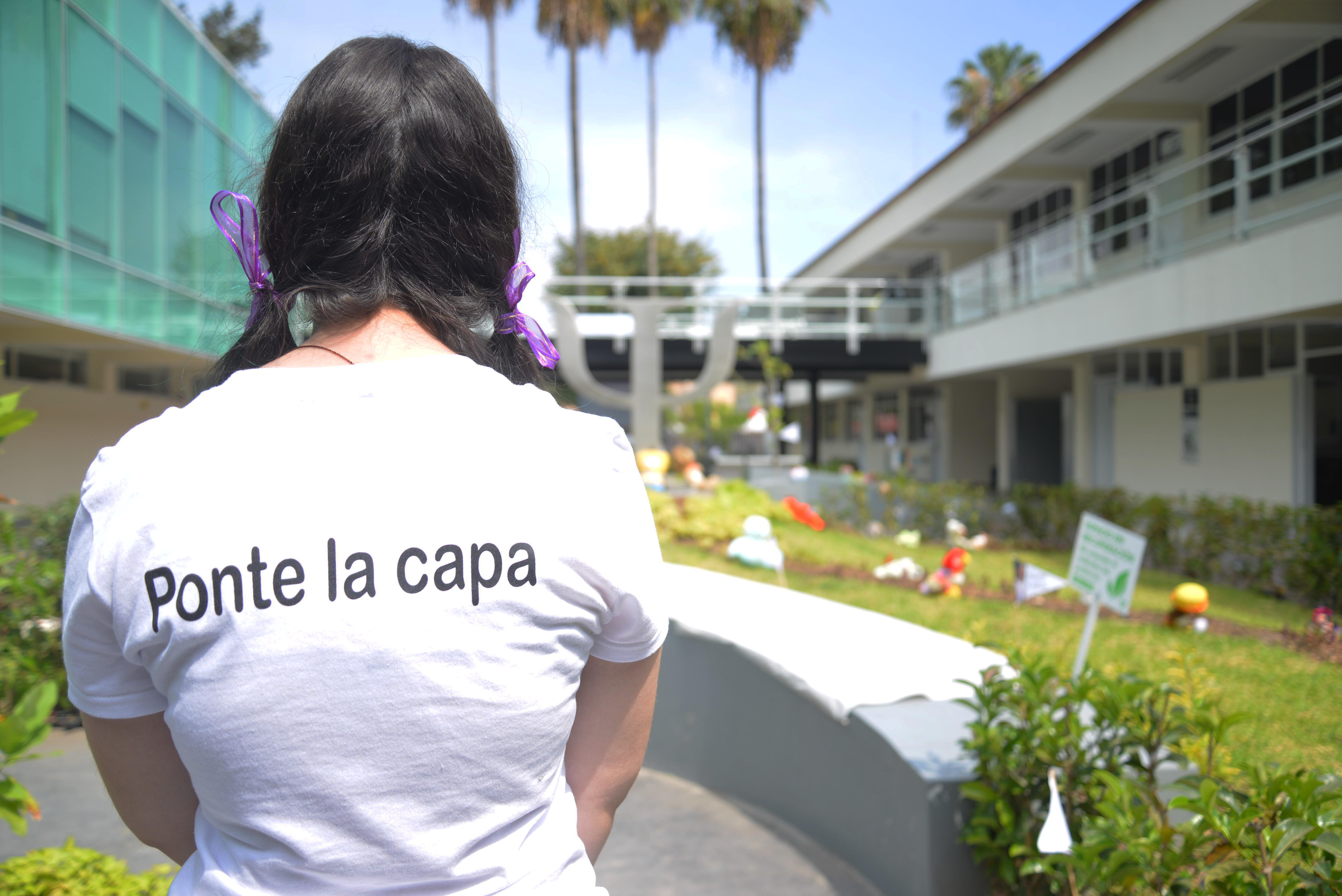 """Alumna exhibiendo playera con leyenda a la espalda """"ponte la capa"""""""