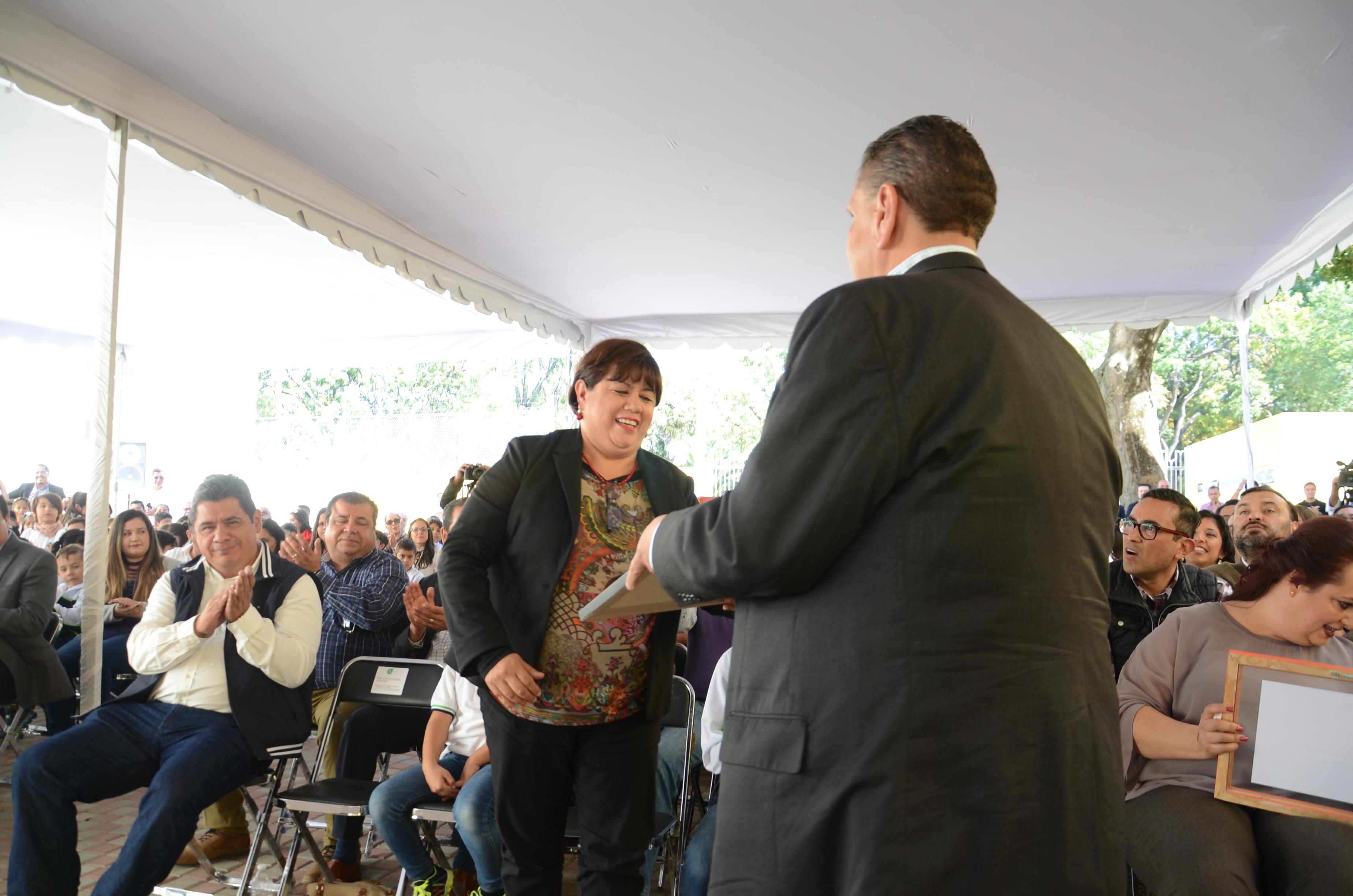Momento en el que el secretario de Educación entrega el reconocimiento a la Dra. Lolita Valadez
