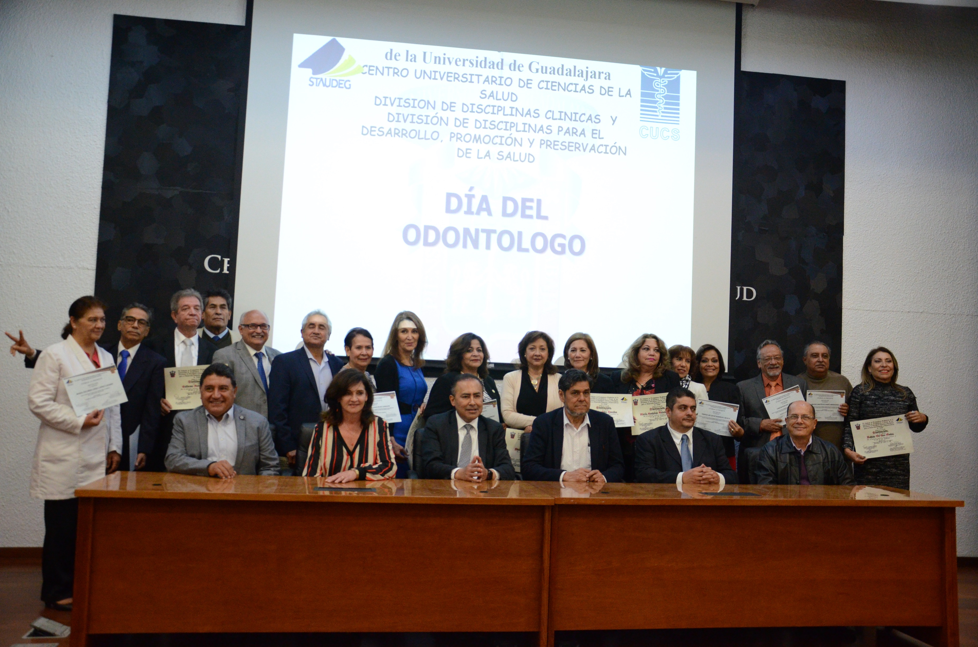 Grupo de odontólogos reconocidos posando para la foto con el rector del CUCS y demás autoridades.