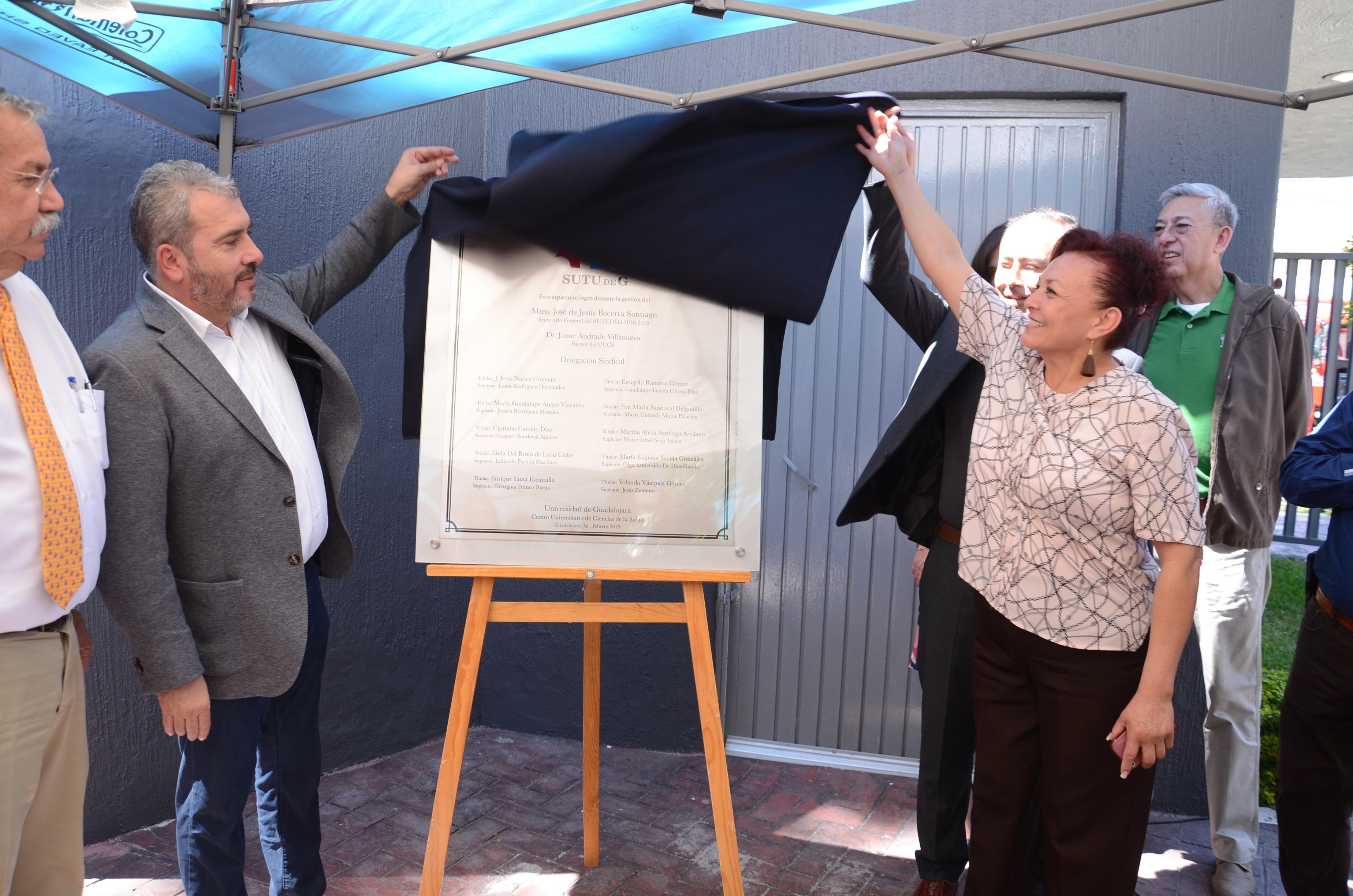 Secretario General y trabajadora del CUCS develando placa