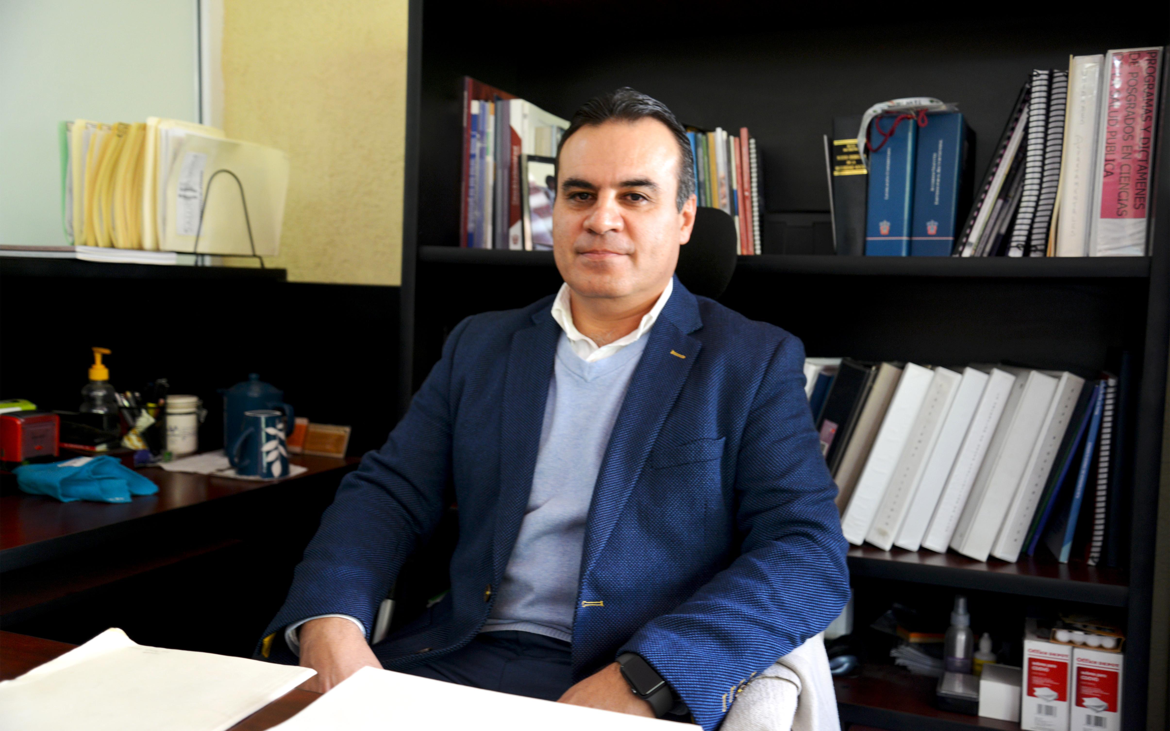 Dr. Igor Ramos Herrera posando para la foto en su oficina, otro ángulo