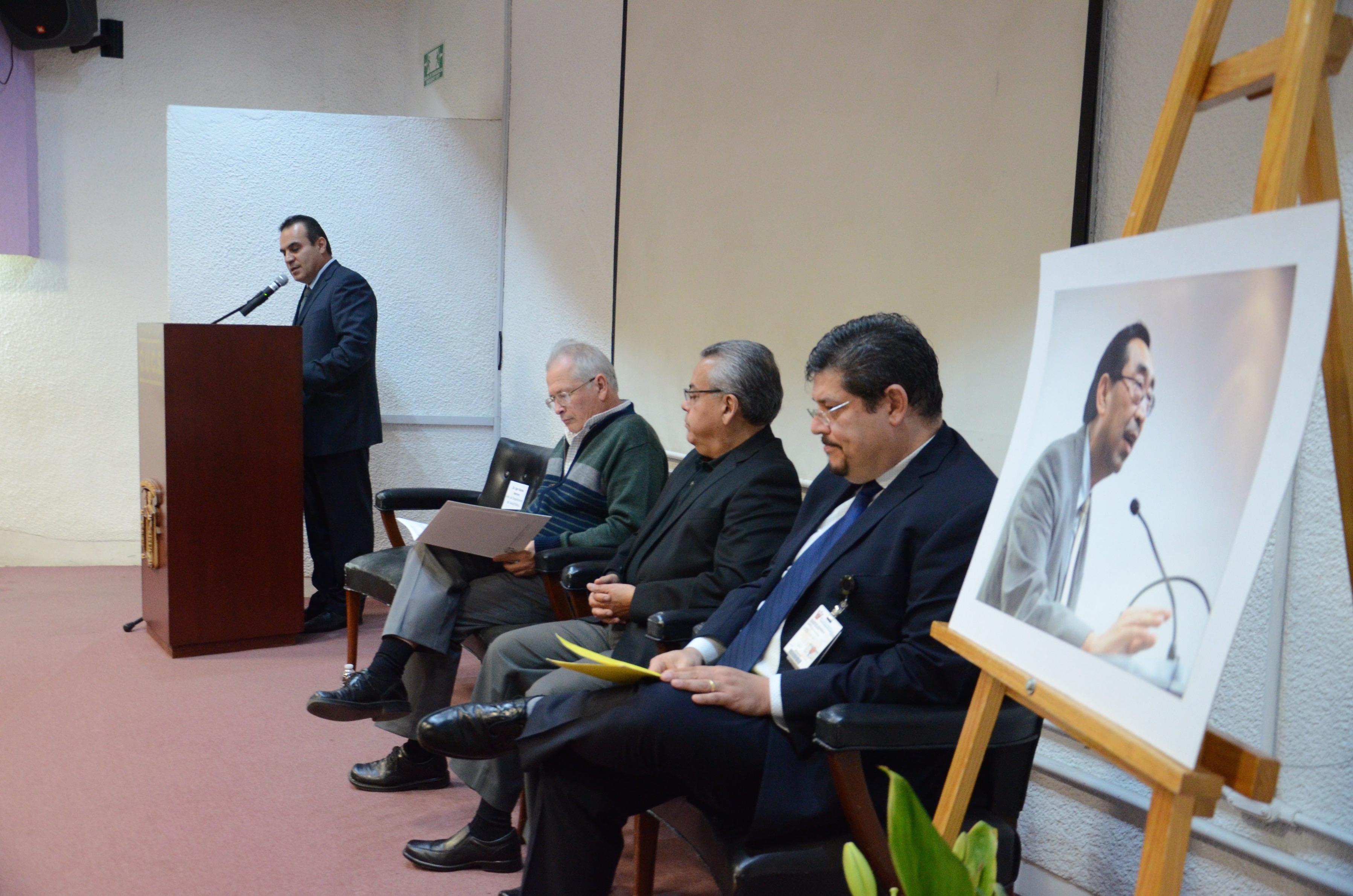 En primer plano fotografía del Dr. Roberto Kumasawa, atrás miembros del presídium