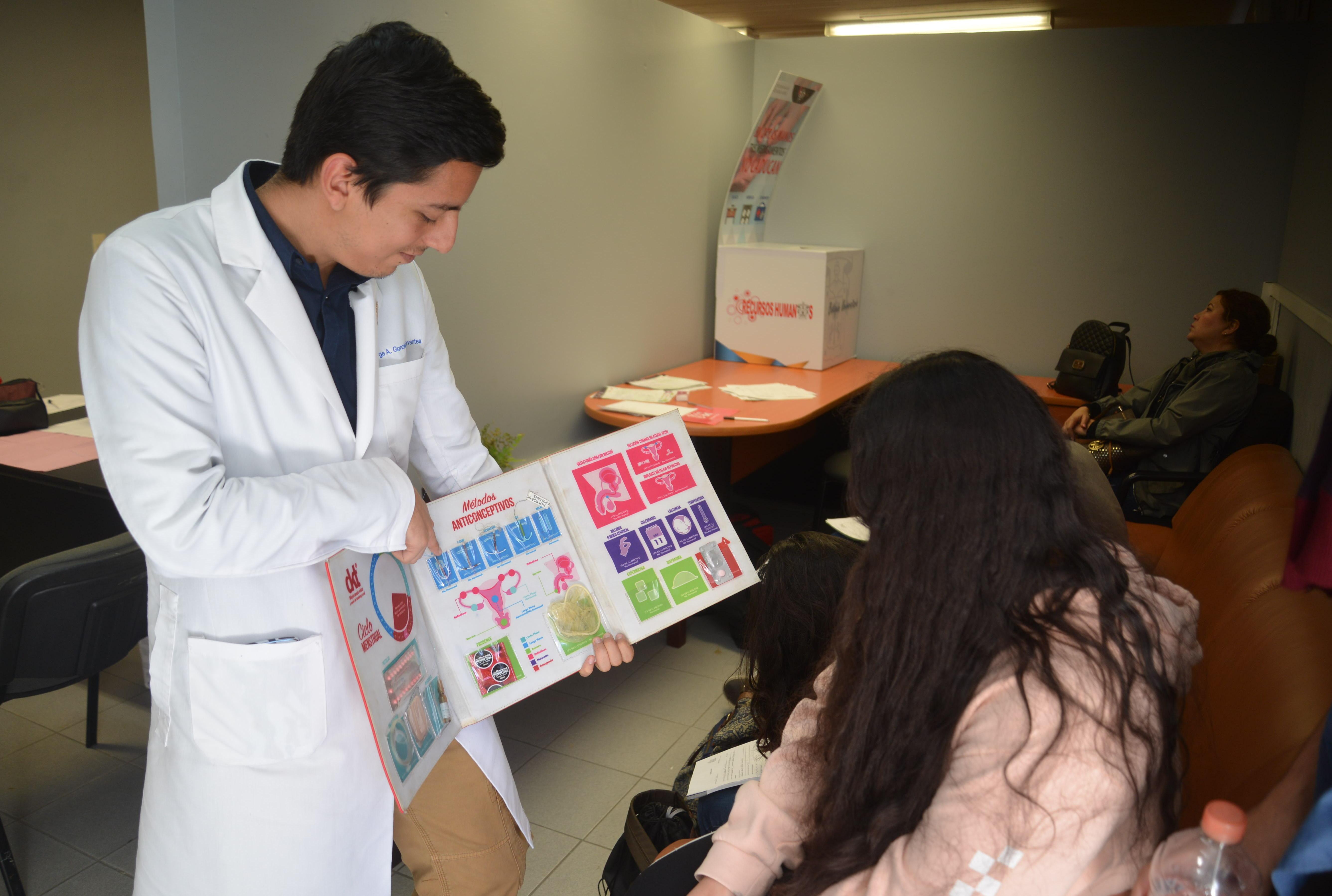 Pasante de medicina ofreciendo consultoría a alumnas del CUCS