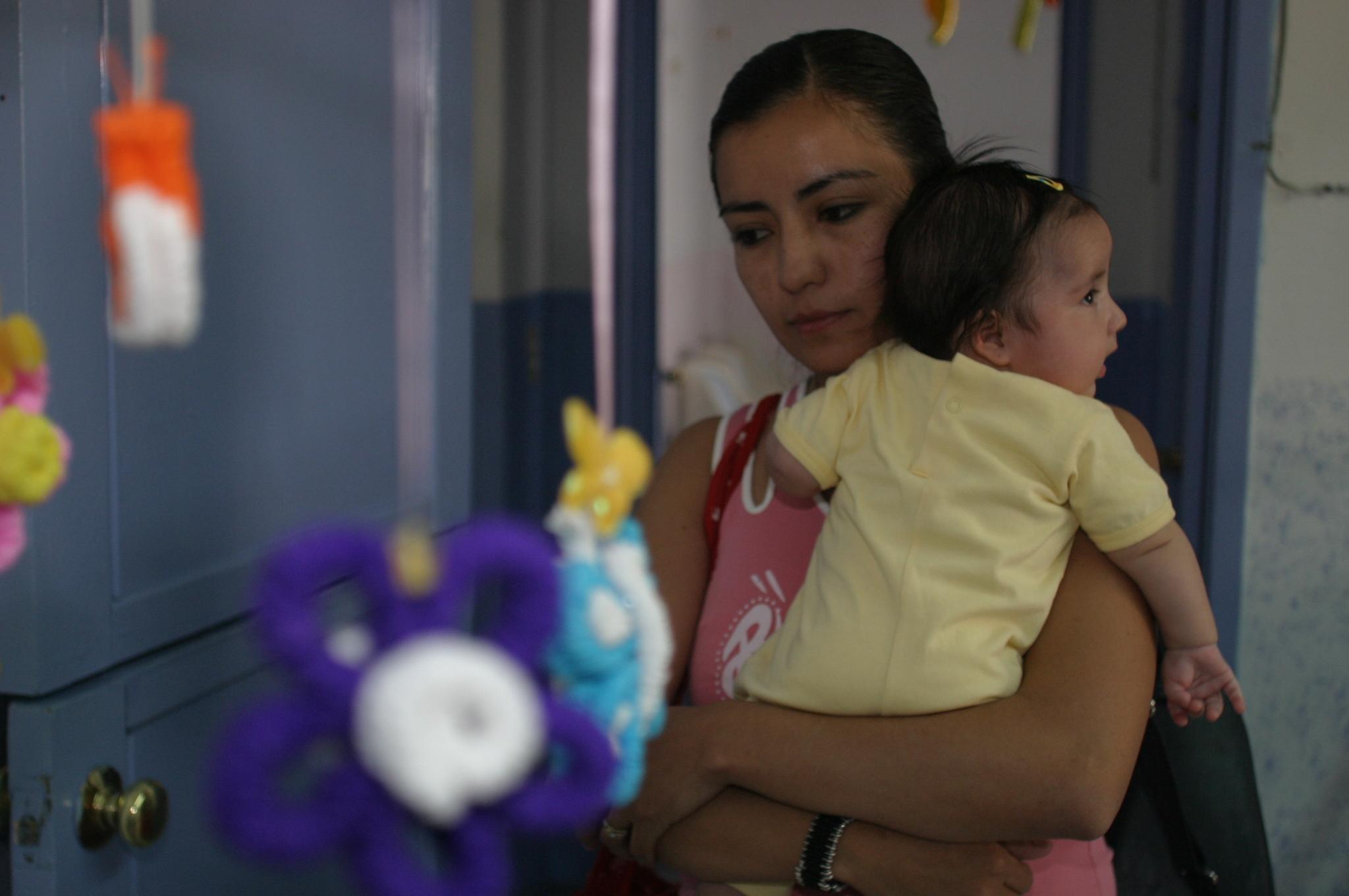 Imagen de una madre cargando a su bebé en una guardería