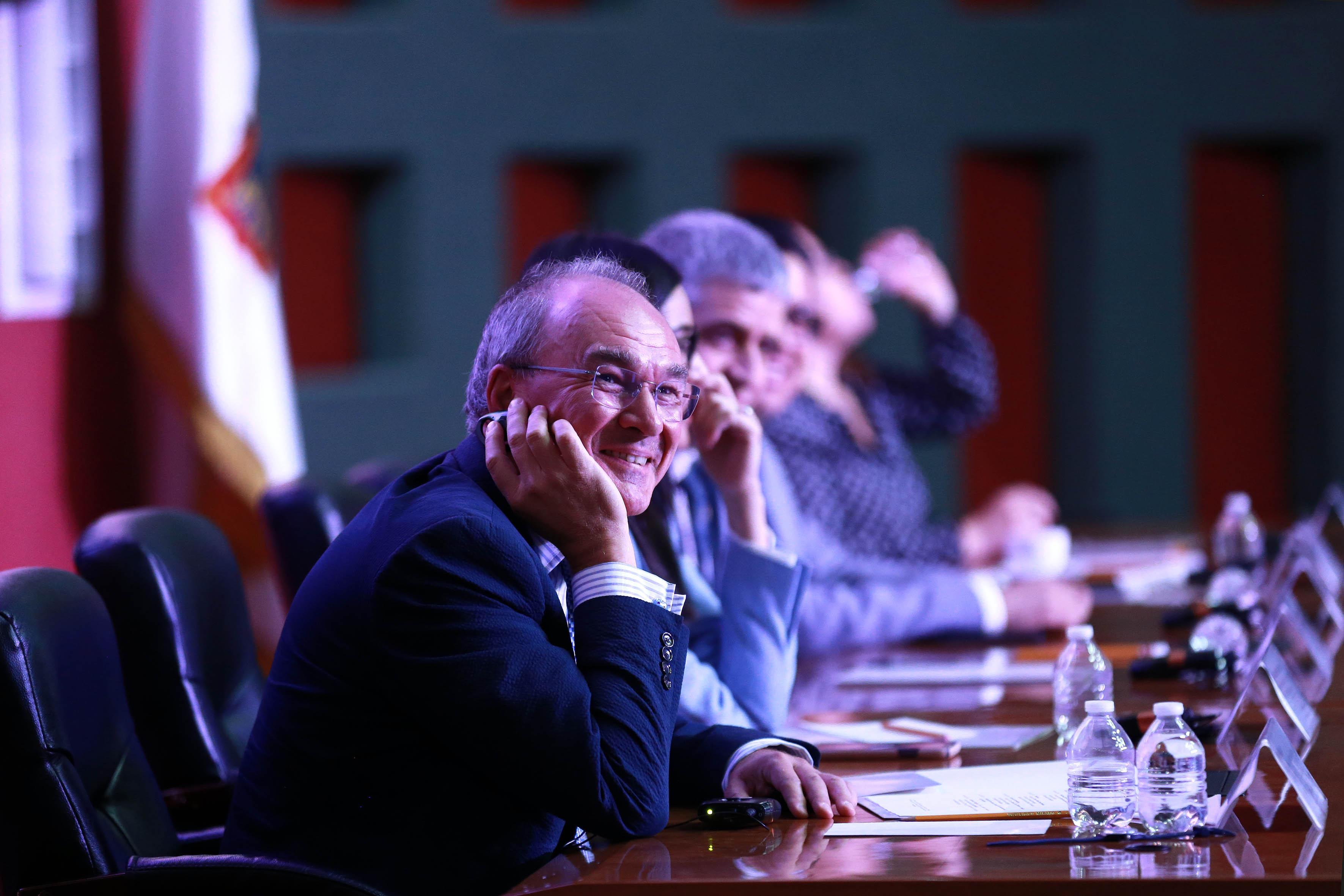 Ponente en la mesa del presídium sonrriendo