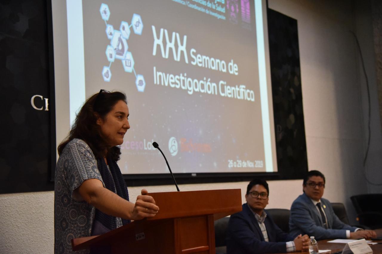 Coordinadora de Investigación dando mensaje en pódium
