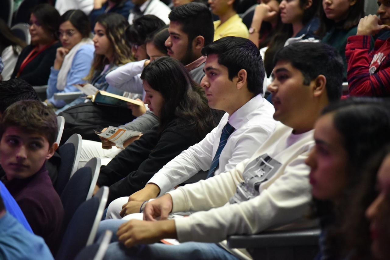 Alumnos con bata blanca atentos a la conferencia