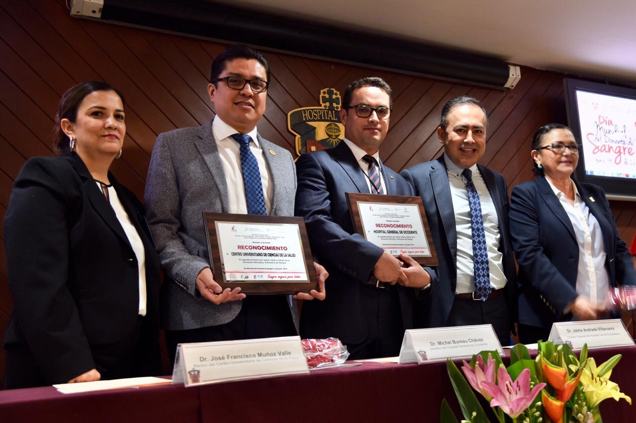 Dr. Muñoz posando con reconocimiento en mano acompañado de otros rectores