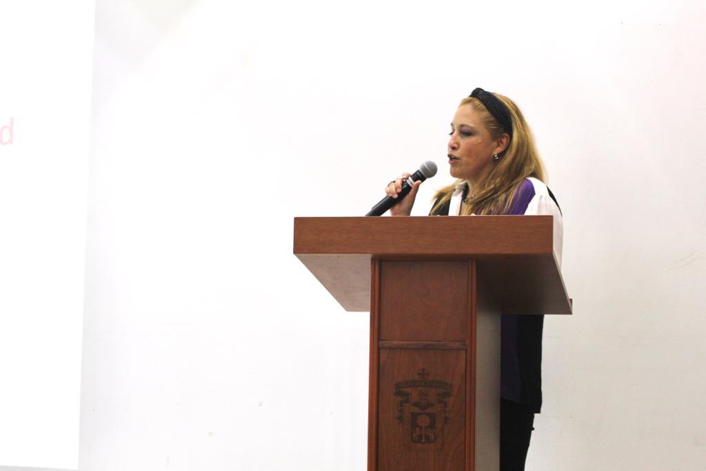 Ponente iniciando su conferencia al micrófono en el pódium